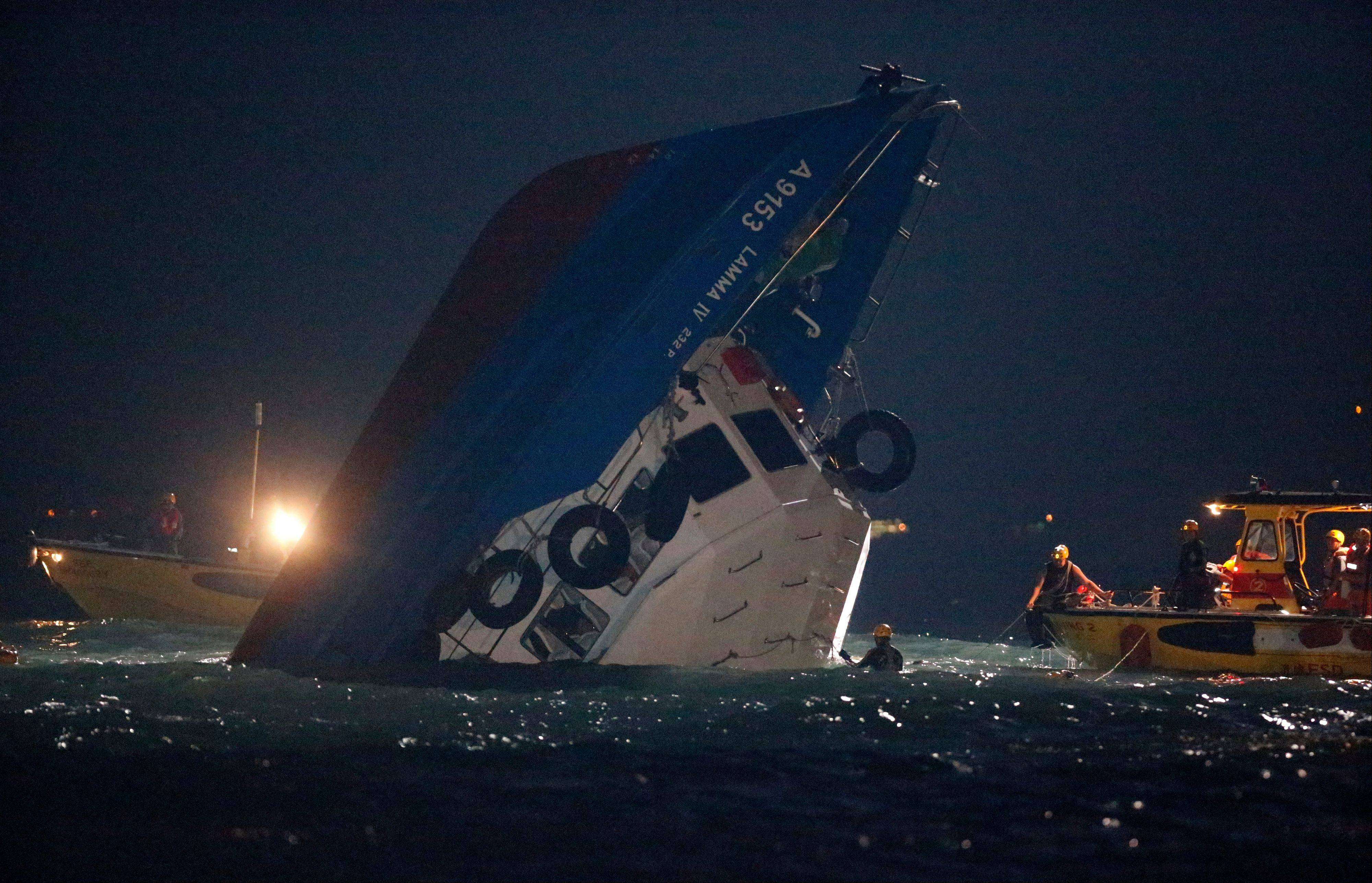 Rescuers check on a half-submerged boat after it collided Monday night near Lamma Island, off the southwestern coast of Hong Kong Island Tuesday, Oct. 2, 2012. Authorities in Hong Kong have rescued 101 people after a ferry collided with a tugboat and sank. A local broadcaster says eight people died.