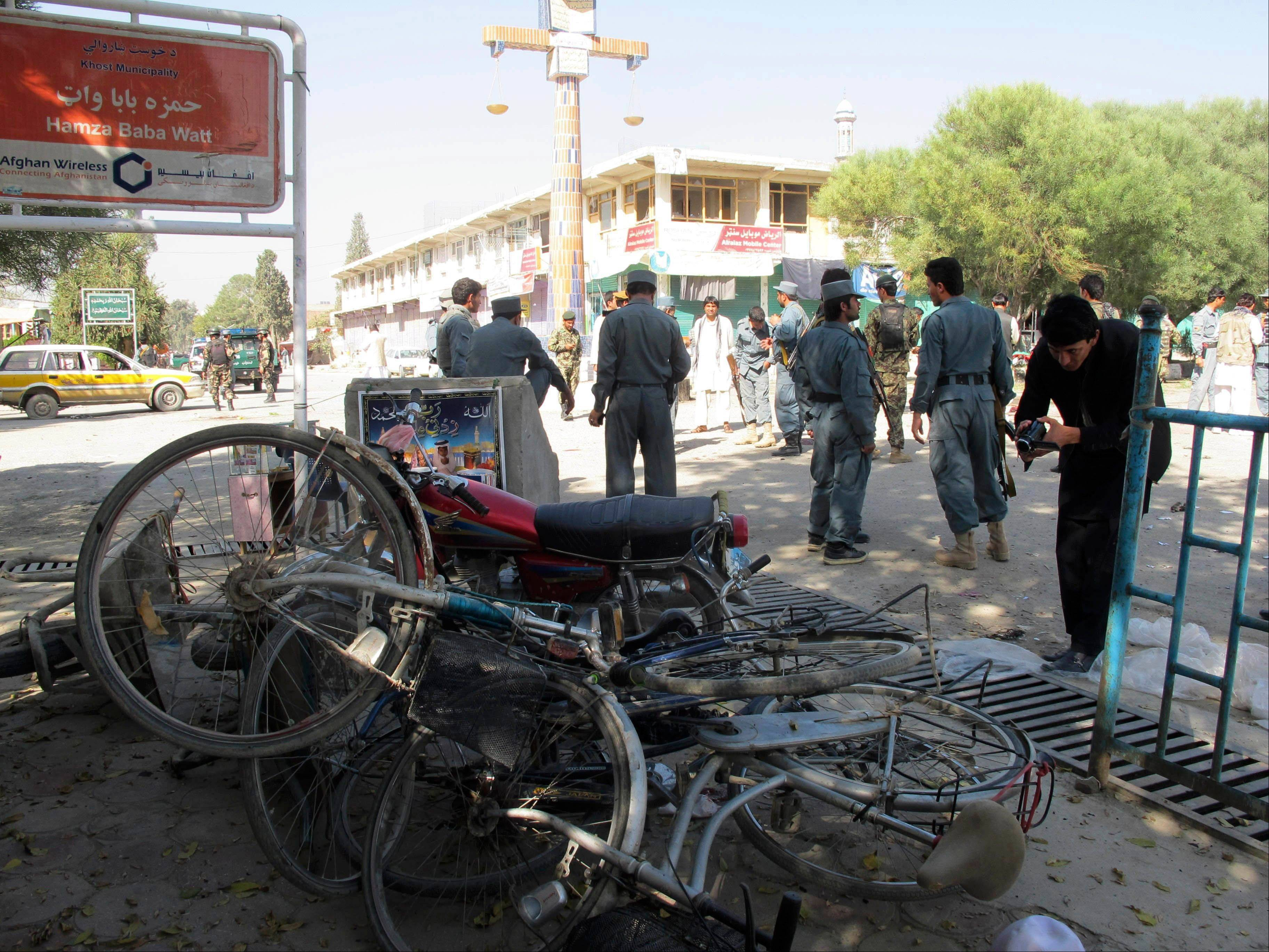 Afghan police secure the site of a suicide bombing in Khost, south of Kabul, Afghanistan, Monday. The suicide bomber was driving a motorcycle packed with explosives and rammed it into a patrol of Afghan and international forces, killing over a dozen people, including three NATO service members and their translator, an official said.