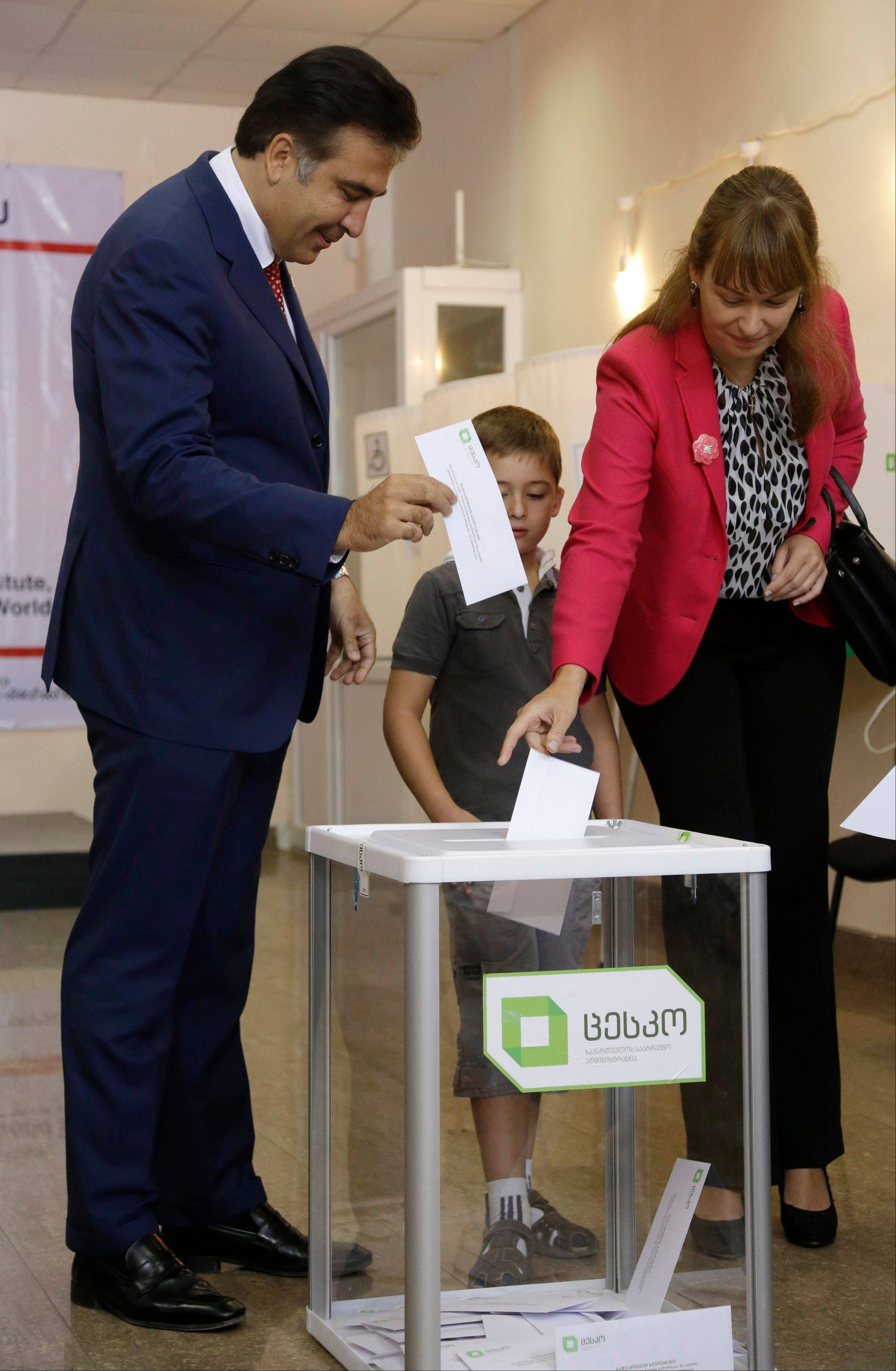 Georgian President Mikhail Saakashvili, left, and his wife, Sandra Roelofs cast their ballots as their son Nikoloz stands beside them at a polling station in Tbilisi, Georgia, Monday. Voters in Georgia are choosing a new parliament in a heated election that will decide the future of Saakashvili�s government.