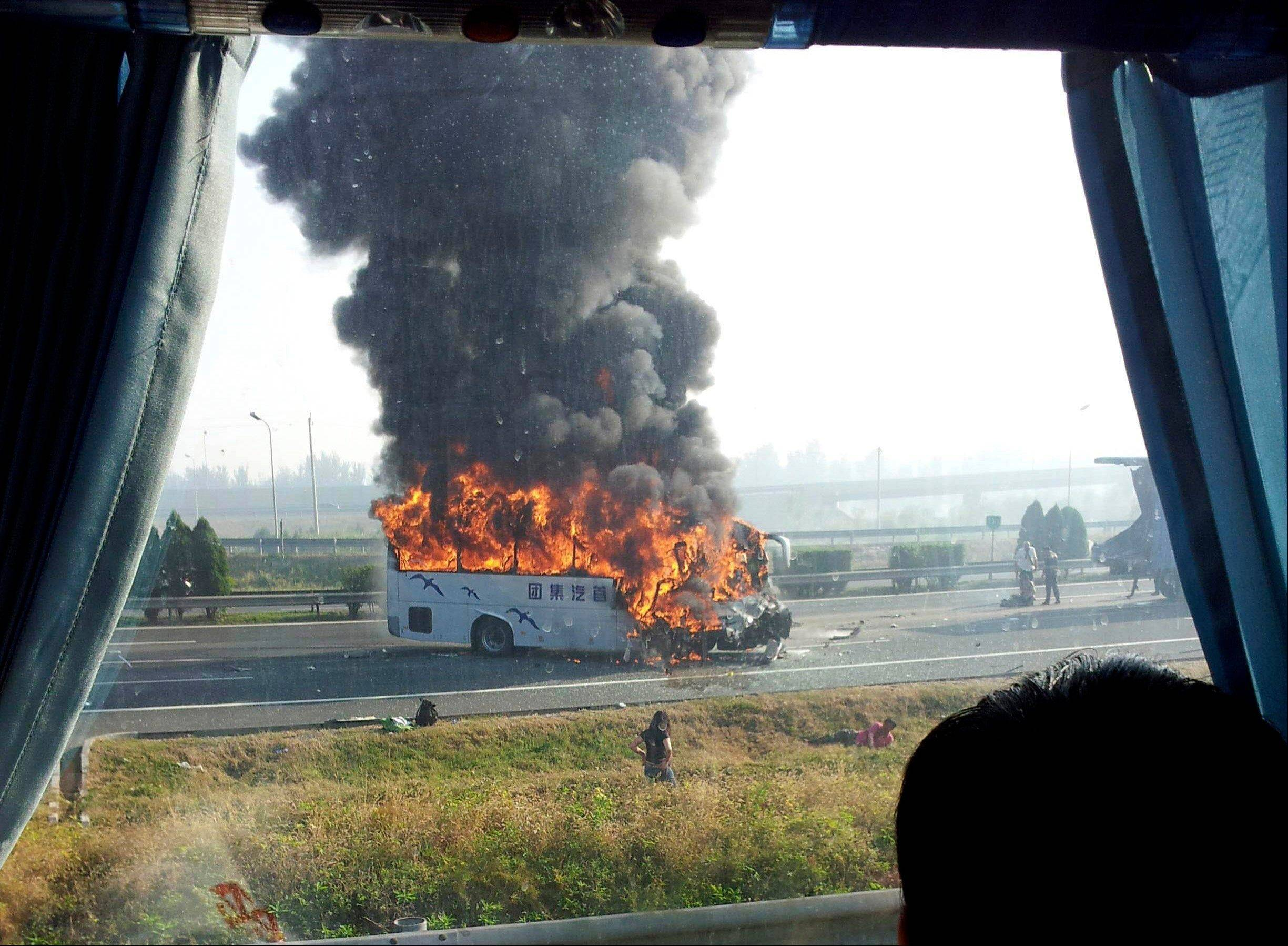 A tourist bus is engulfed in flames on an expressway near Tianjin, China, Monday. Five Germans and a Chinese citizen were killed when the bus burst into flames after hitting the back of a truck, the Xinhua News Agency said.
