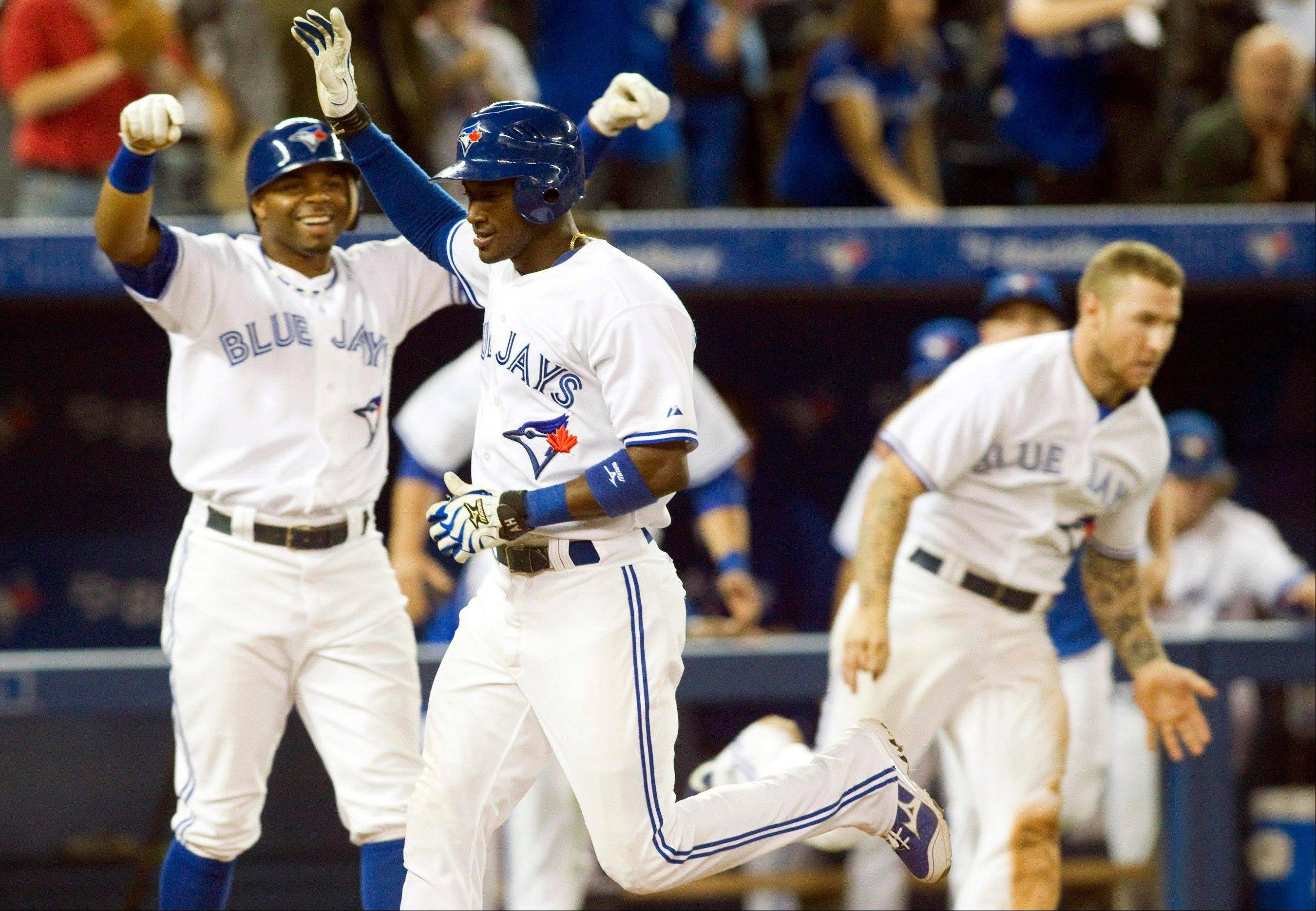The Blue Jays� Adeiny Hechavarria, center, celebrates scoring on Anthony Gose�s hit a game-winning single against the Minnesota Twins during the 10th inning Monday in Toronto.