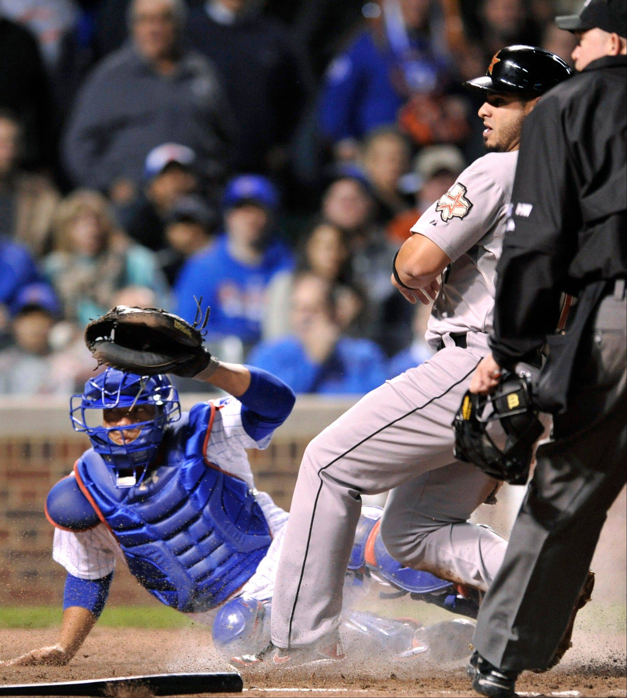 Houston Astros' Fernando Martinez center, crosses home plate safely as Chicago Cubs catcher Welington Castillo left, misses the throw and home plate umpire Ron Kulpa looks on in the fourth inning during a baseball game in Chicago, Monday, Oct. 1, 2012. Houston won 3-0.