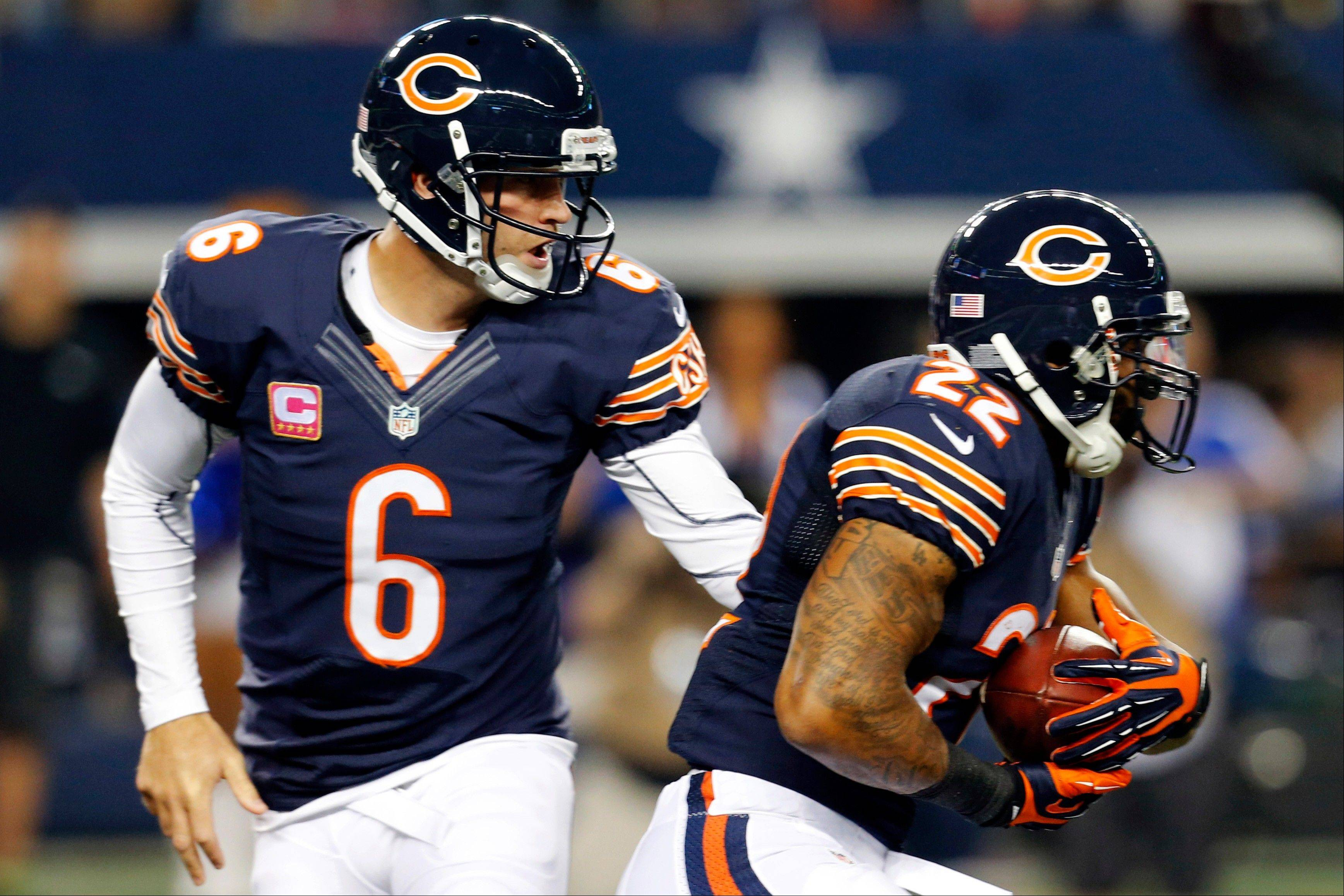 Chicago Bears� Jay Cutler hands off to running back Matt Forte in the first half.