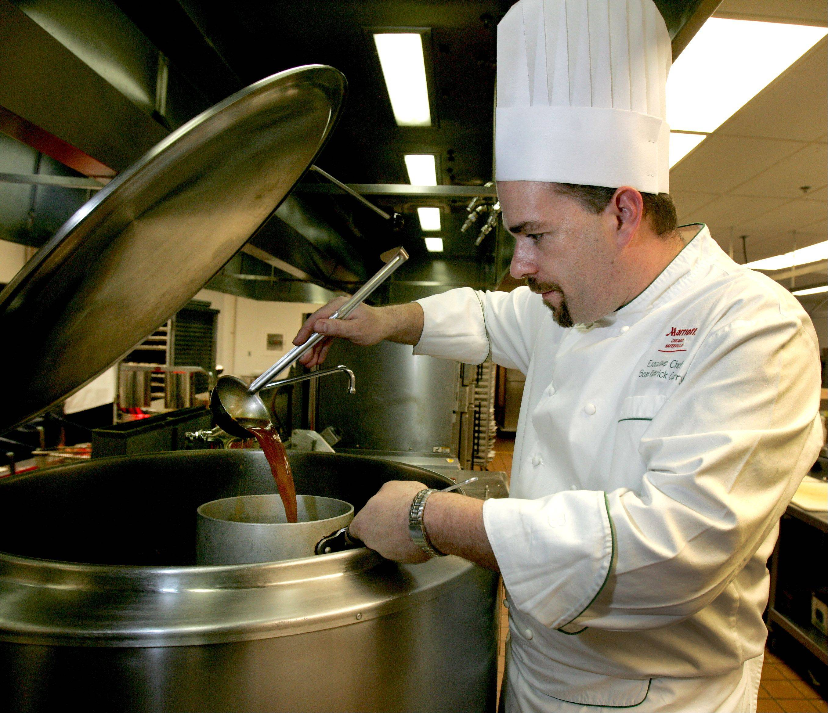 Bev Horne/bhorne@dailyherald.comExecutive chef Sean Patrick Curry at work in the kitchen at Artisan Table restaurant in Naperville.