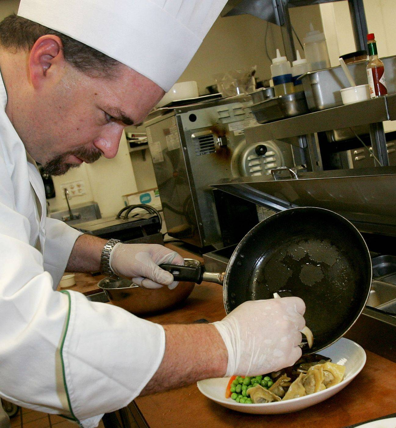 Chef Curry prepares a plate of shortrib tortellini for diners at Artisan Table in Naperville.
