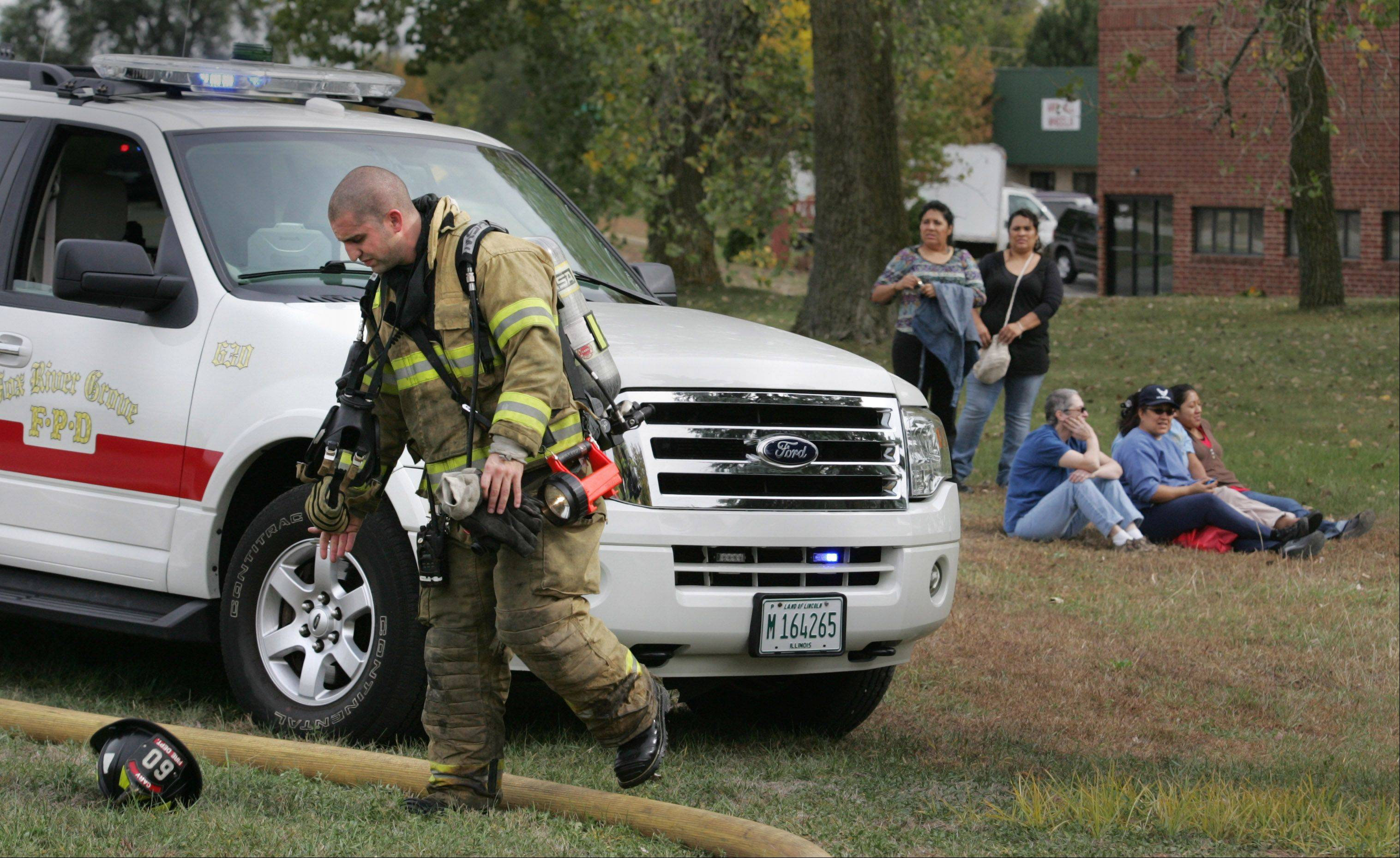 Cary firefighter Tony Diraimondo removes some of his gear after working inside the Tru-Cut factory building in Cary Monday afternoon. Plant employees sit in the grass behind him as fire departments work at the scene.