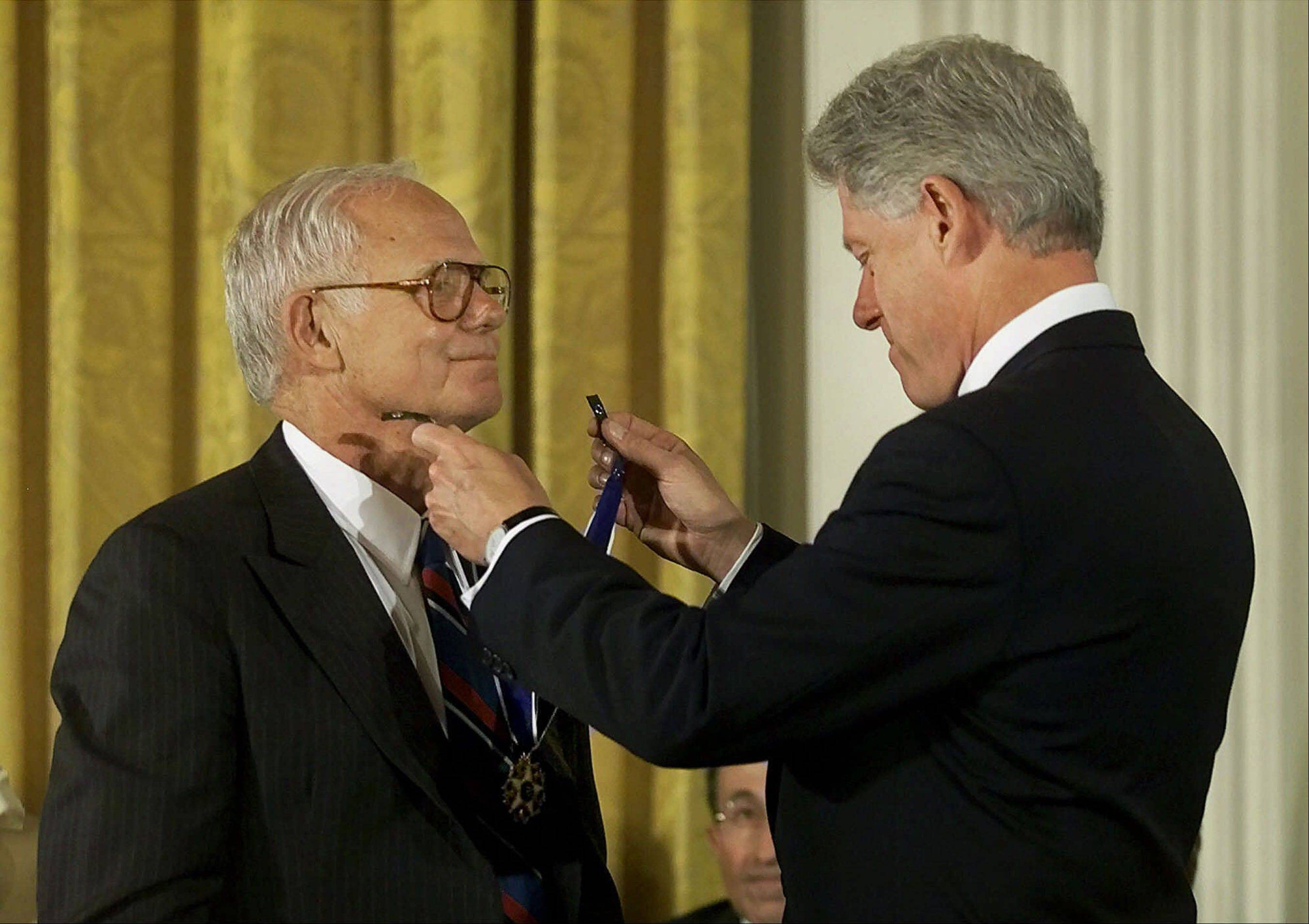 In an Aug. 9, 2000 photo provided by Johnson & Johnson, President Bill Clinton, right, awards former Johnson & Johnson CEO James E. Burke the Presidential Medal of Freedom, in Washington. Burke, who helped the company expand dramatically around the world and steered it through the Tylenol poisonings in the 1980s, died on Friday, Sept. 28. He was 87.