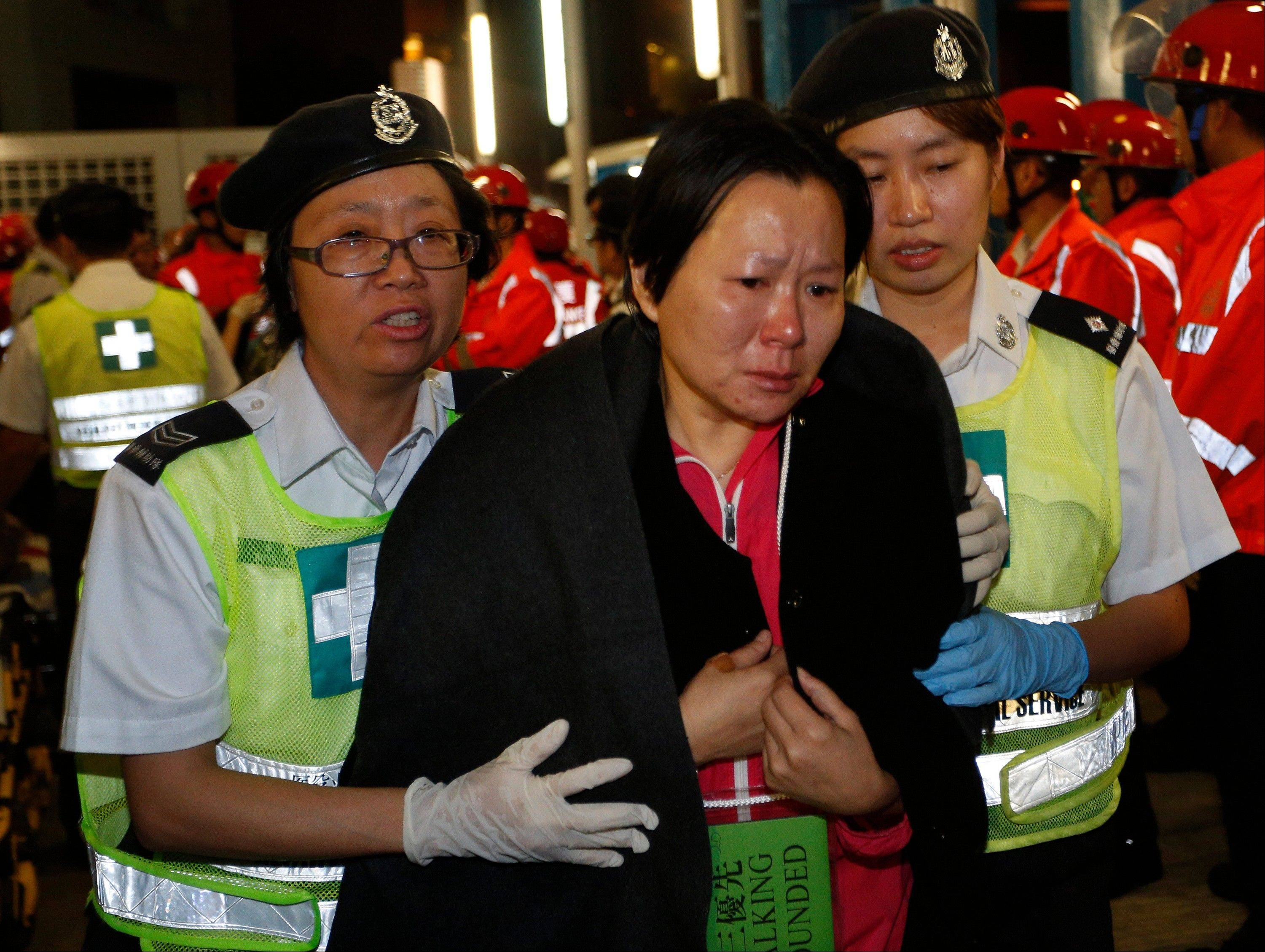 A survivor supported by rescuers, is taken onto shore after a collision involving two vessels in Hong Kong Tuesday, Oct. 2, 2012. Authorities in Hong Kong have rescued 101 people after a ferry collided with a boat and sank. A local broadcaster says eight people died. The government said in a statement that the ferry was carrying about 120 people when the accident happened Monday night near Lamma Island, off the southwestern coast of Hong Kong Island. Few other details were given.