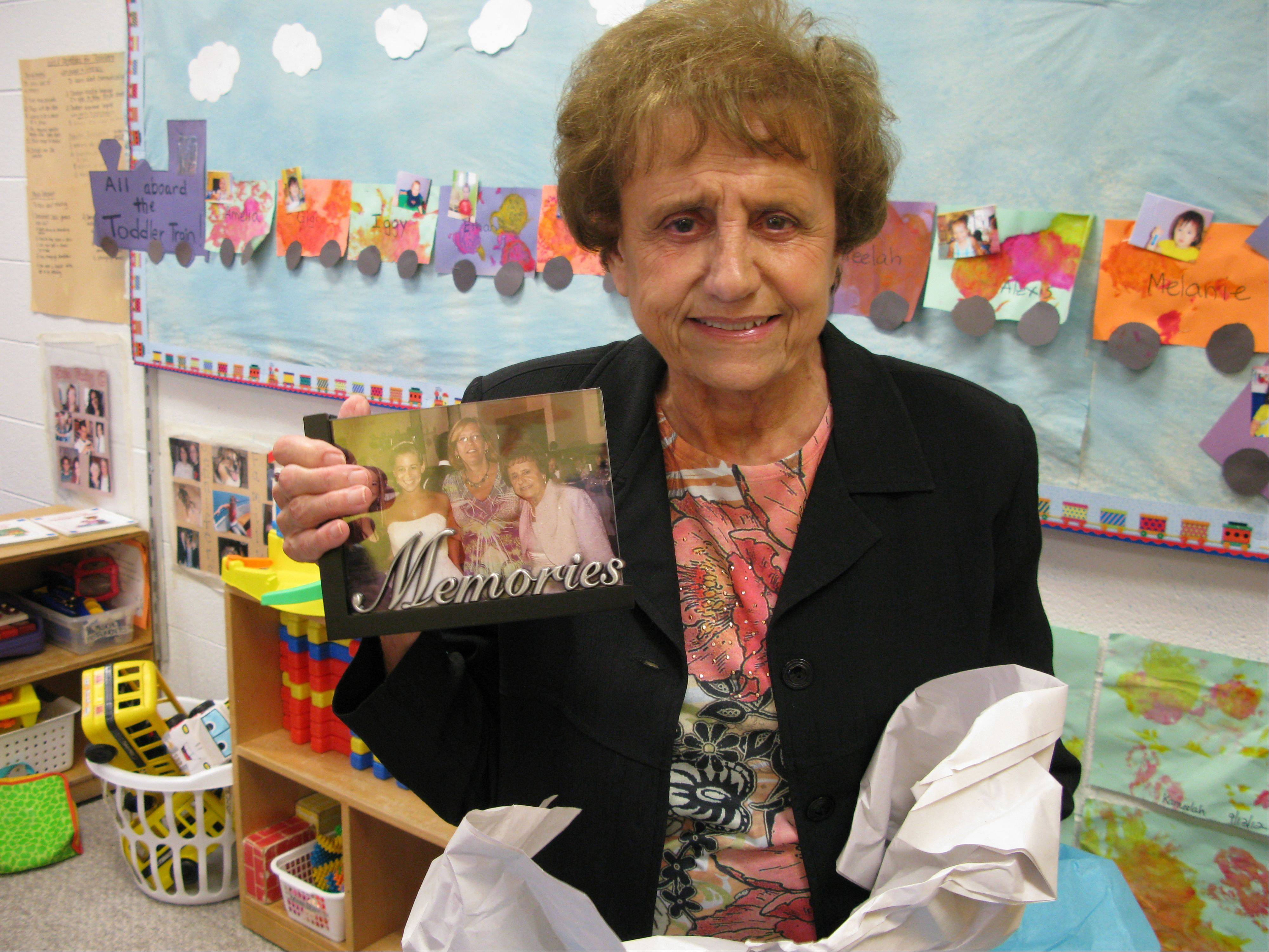 Marie Handley, 88, holds up a keepsake photograph gifted by co-workers upon her retirement Wednesday after working 26 years at the Elk Grove Township Community Day Care Center.