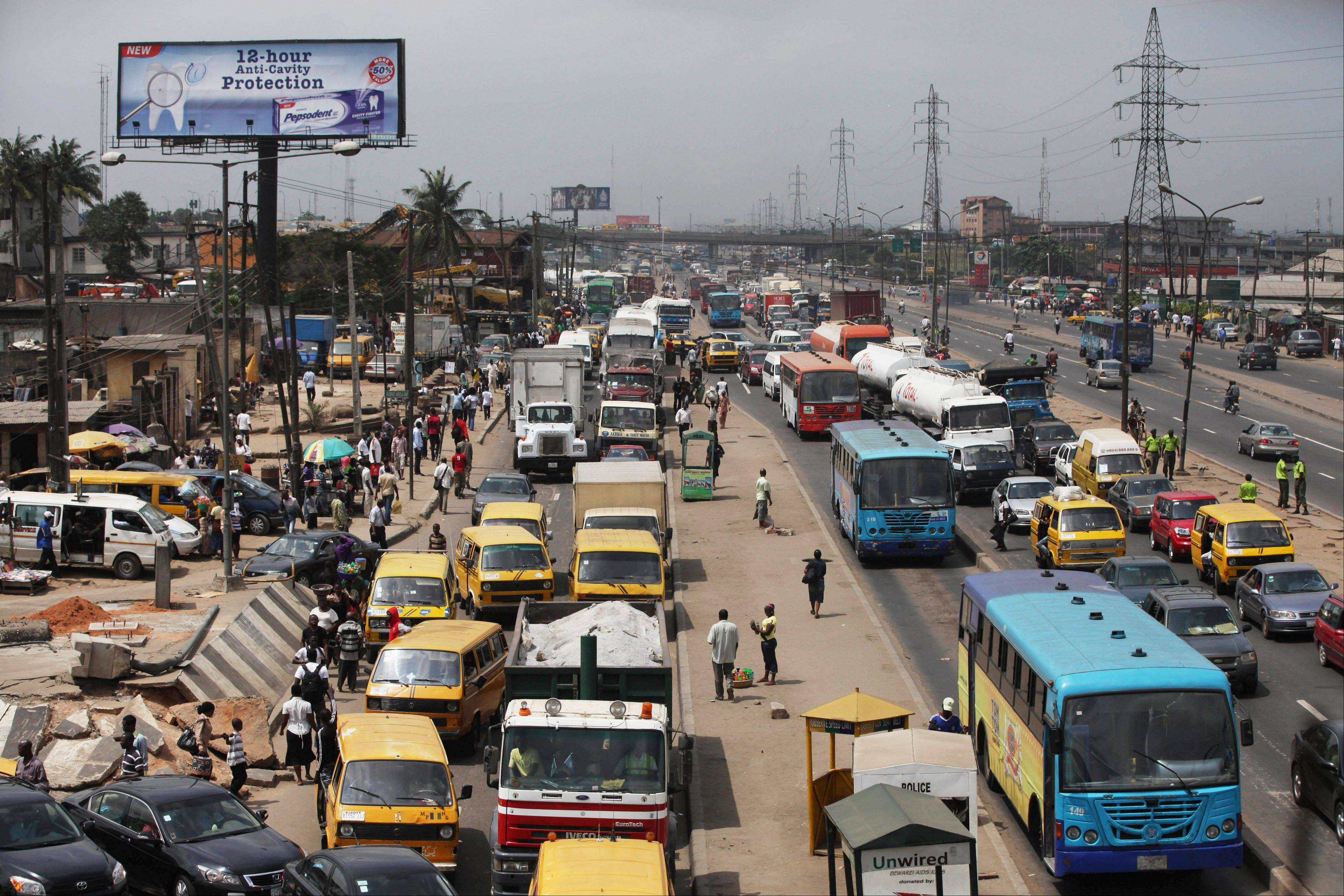 "Traffic backs up along a busy road in Lagos, Nigeria. In the metropolis of 17.5 million, the traffic jams that Nigerians call ""go-slows"" can strike at any moment. Here, drivers are hostage to a road network that hasn't been upgraded since the 1970s."