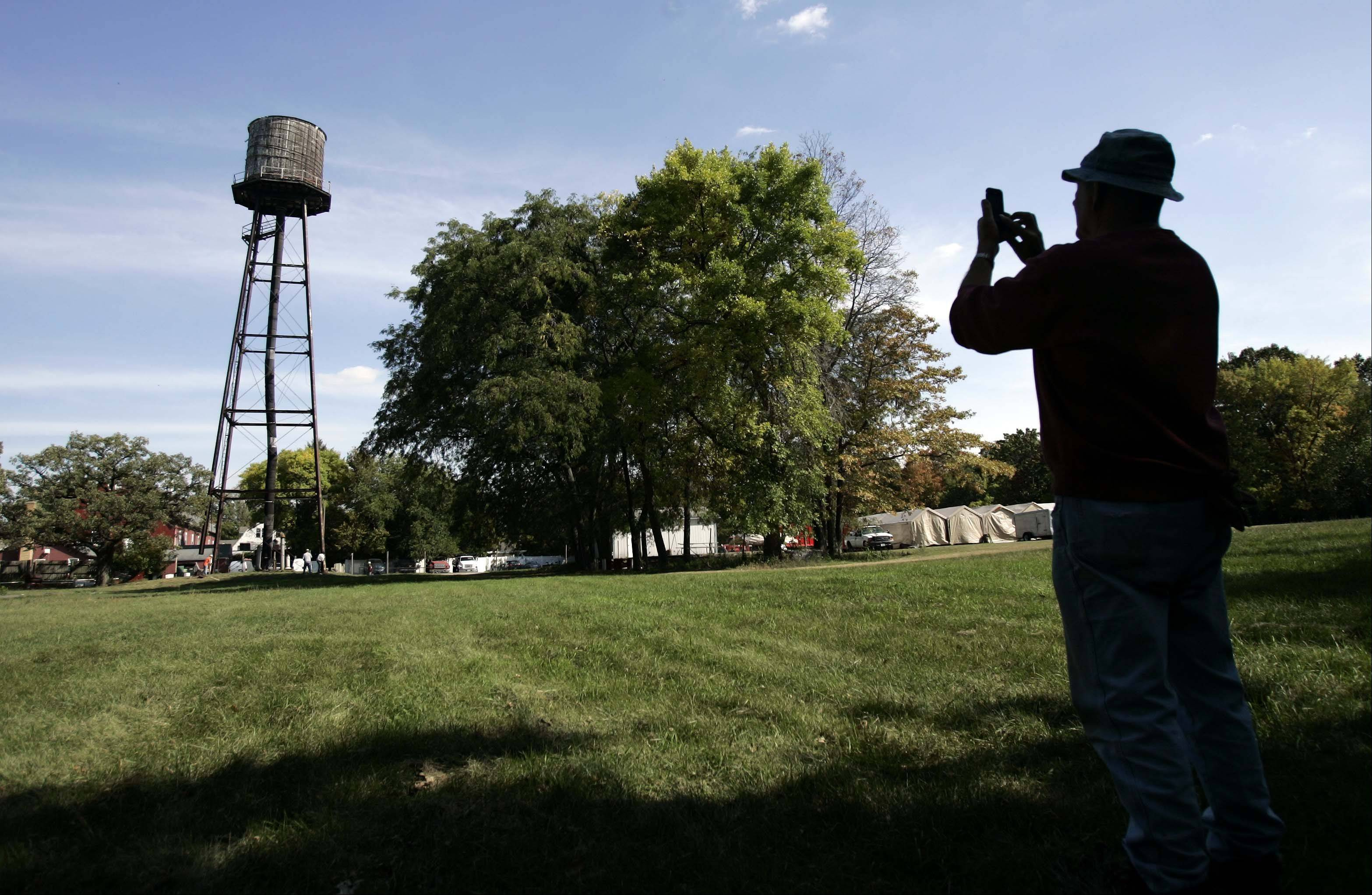 BRIAN HILL/bhill@dailyherald.comOwner Bruce Oehlerking takes some last minute photos of the water tower as Able Contractors takes down the 40,000 gallon water tower that was used for the fire sprinkler system at the Milk Pail in un-Incorporated Kane County Tuesday September 25, 2012. The 120 foot tall tower which was built in 1952 functioned until the early 90s when they connected to East Dundee water system.