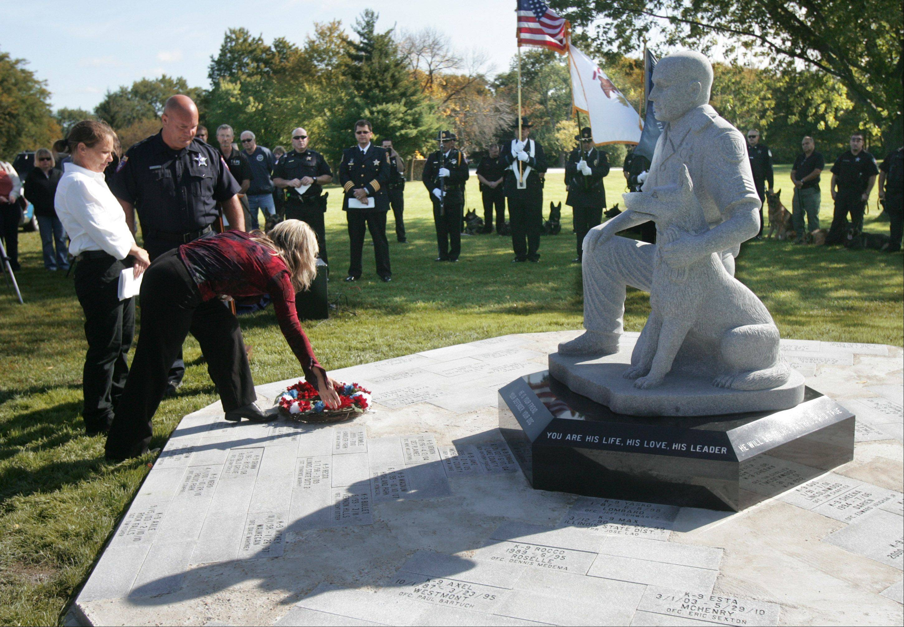 Gilbert R. Boucher II/gboucher@dailyherald.comTraci Sikorski places a wreath at the memorial with Paula Rothacker and Anthony Fanella, members of the memorial committee, during the first annual ceremony for the Northern IL Police K-9 Memorial Wednesday at Highland Memorial Park Cemetery in Gurnee. A memorial statue was unveiled and 79 dogs were given tribute for their service.
