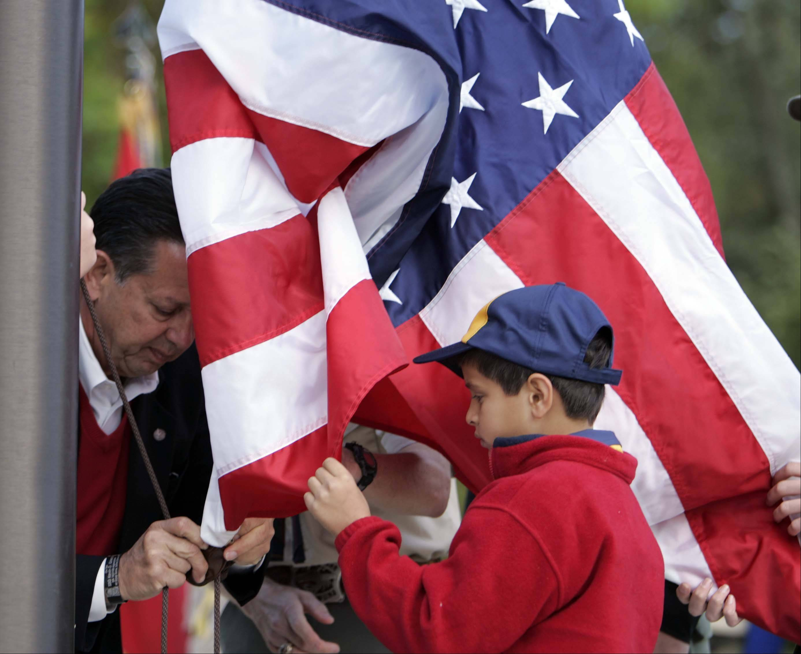 BRIAN HILL/bhill@dailyherald.comRalph Grieco (father of Kevin) helps his grandson Joshua, 8, attach and raise the American flag during the ceremony. The Three Fires Council-Boy Scouts of America honor Eagle Scout and Illinois National Guardsman Kevin D. Grieco with a plaque and flagpole dedication at Camp Big Timber in Elgin Saturday September 22, 2012. Grieco who was an assistant scout master to Troop 575 in Winfield was killed in Afghanistan in 2008.