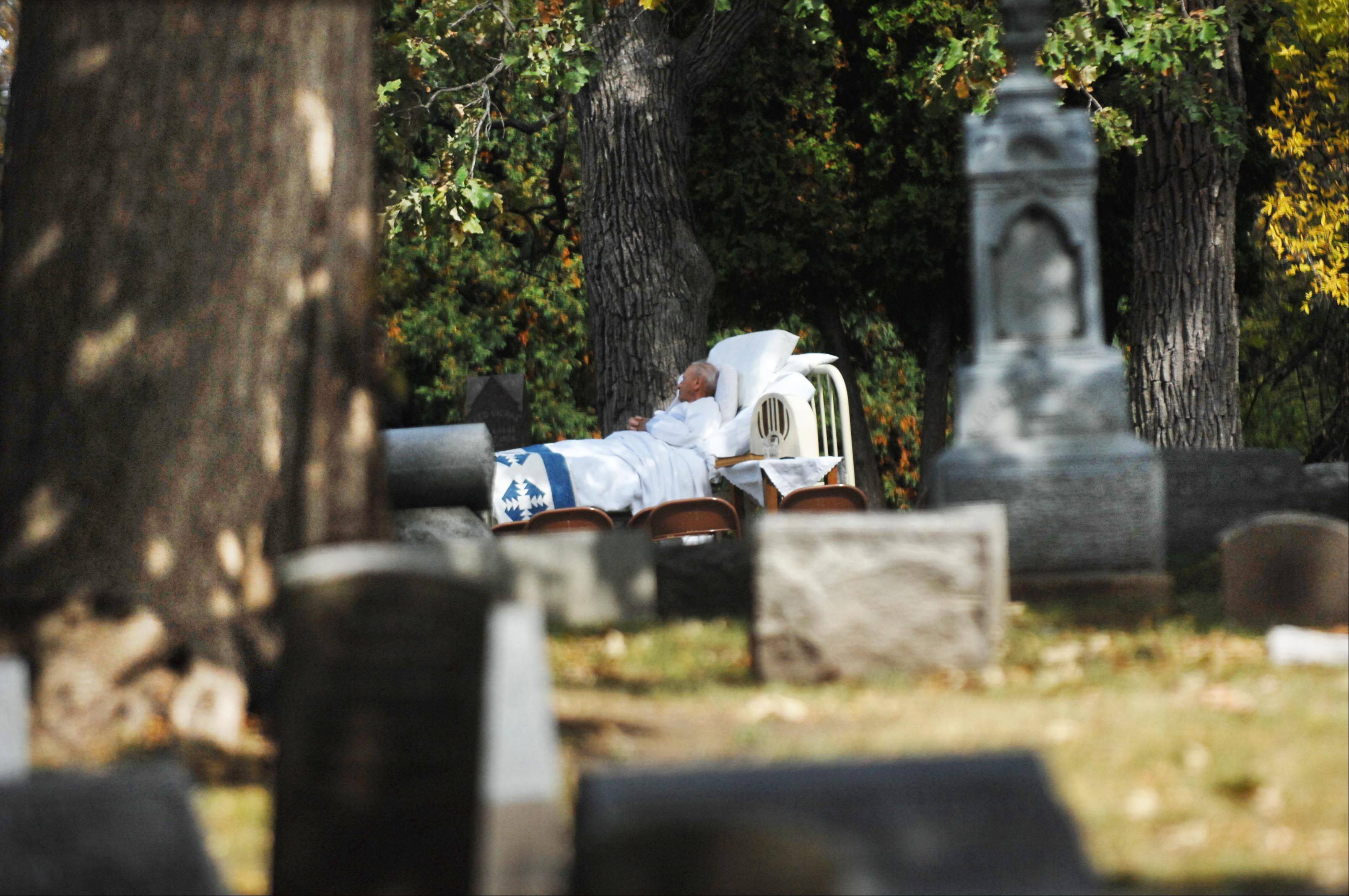 "John Starks/jstarks@dailyherald.comJim Anderson lays in an antique bed on a hill in Bluff City Cemetery Sunday during the 25th Annual Cemetery Walk. He was portraying Francis ""Shanty"" Pask, who was a carpenter paralyzed in a fall, and whose wife Maryann donated a house to Sherman Hospital with the stipulation that her husband would be cared for until his death. He died in 1940. She died in 1919, and was portrayed by Maryann Pask. The Elgin Historical Society sponsors the event every year."