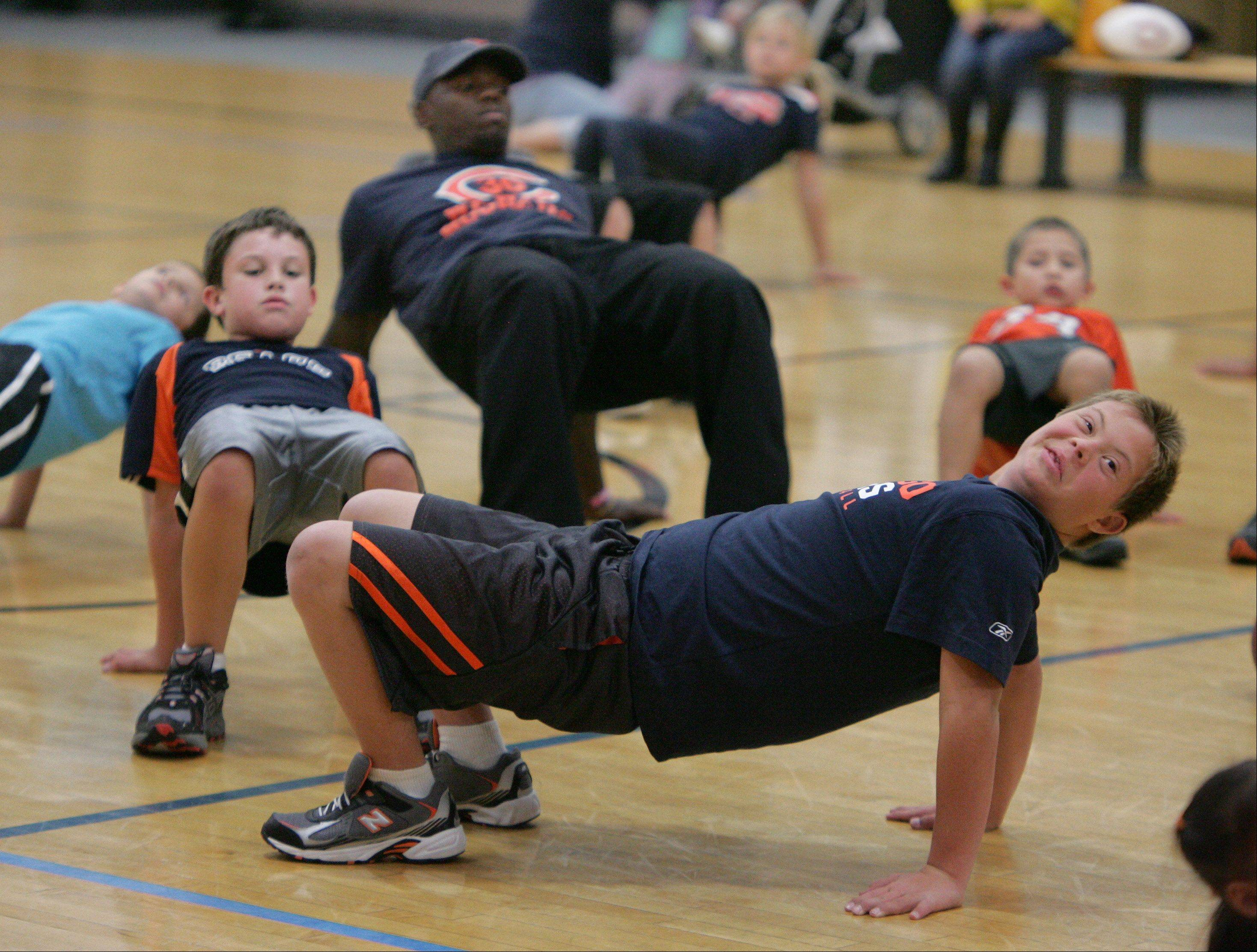 Gilbert R. Boucher II/gboucher@dailyherald.comBrett Wilkinson, 13, of Arlington Heights, makes a back bridge as he exercises with Chicago Bears cornerback D.J. Moore and other children Monday at the Midtown Athletic Club in Palatine as part of the Fuel Up to Play 60 fitness program. The 10th Annual Midtown 5k Run and Walk will kickoff on Saturday, September 29th, to raise money for the Bears Care charity.
