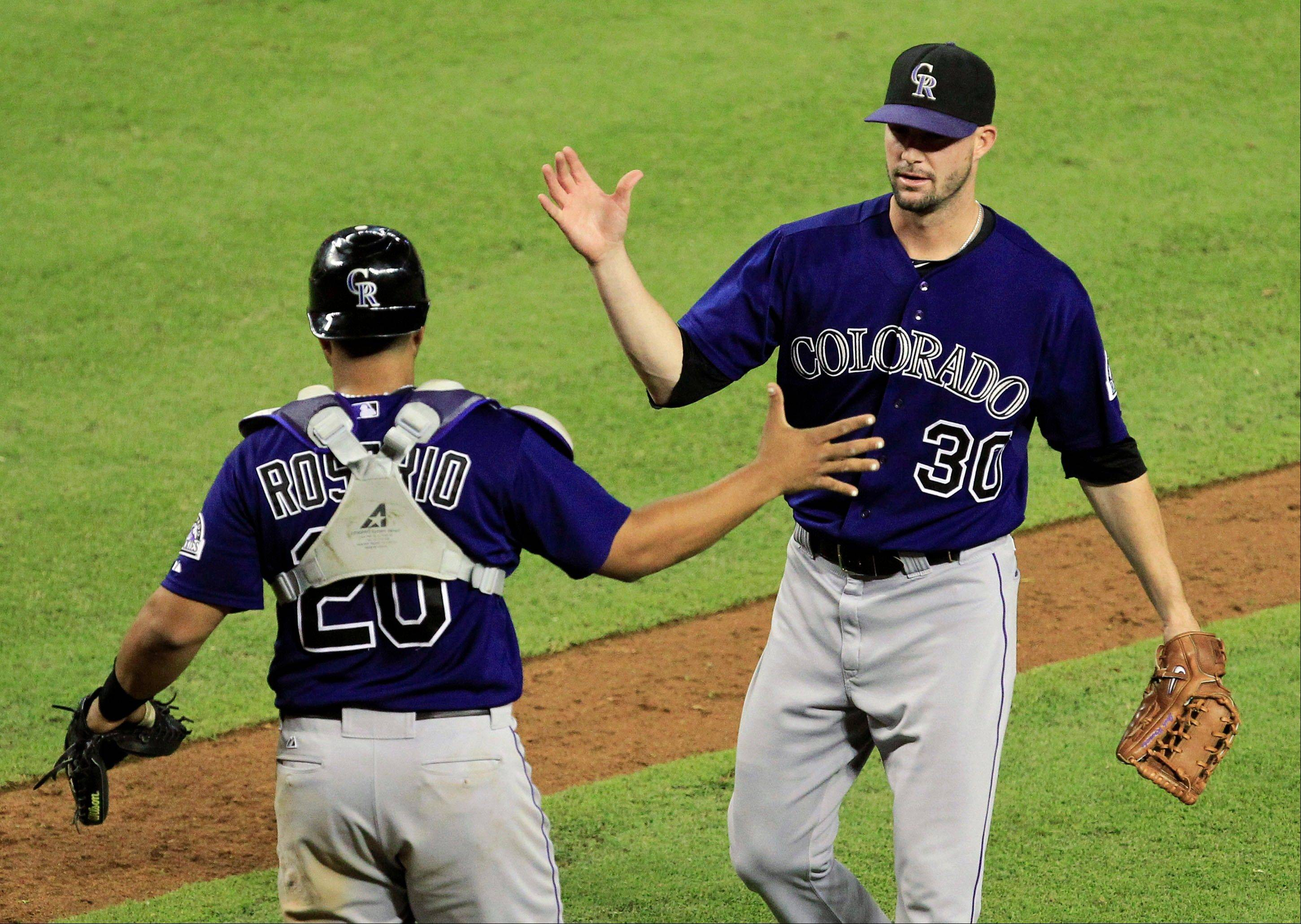 Colorado's Josh Roenicke and Wilin Rosario high-five after a 13-inning win Monday night over the Diamondbacks in Phoenix.