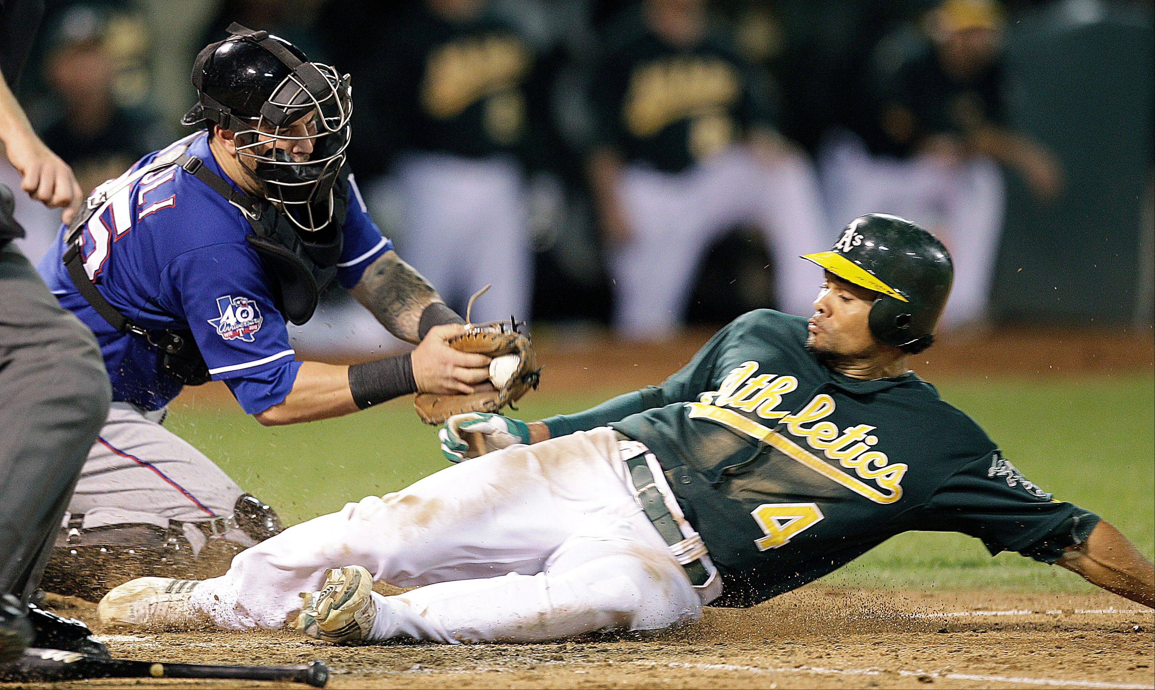 The Athletics' Coco Crisp scores past the tag of Texas Rangers catcher Mike Napoli in the fifth inning Monday in Oakland, Calif.