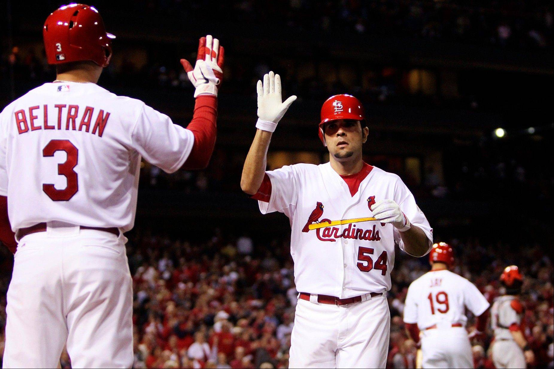 The Cardinals' Carlos Beltran congratulates Jaime Garcia on his solo home run against the Cincinnati Reds in the third inning Monday in St. Louis.
