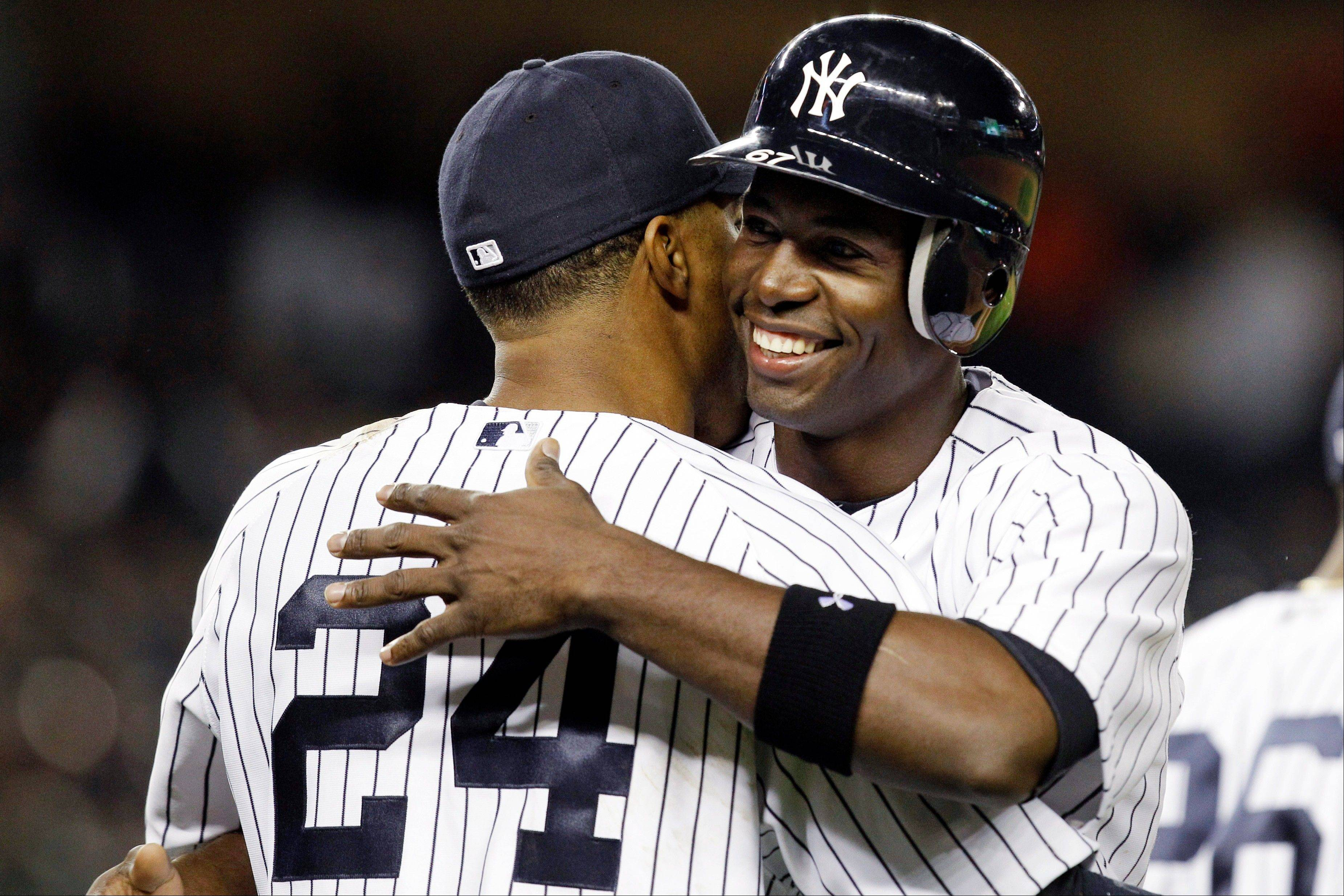The Yankees' Robinson Cano embraces Melky Mesa after Mesa drove in a run on his first major-league hit Monday in New York.