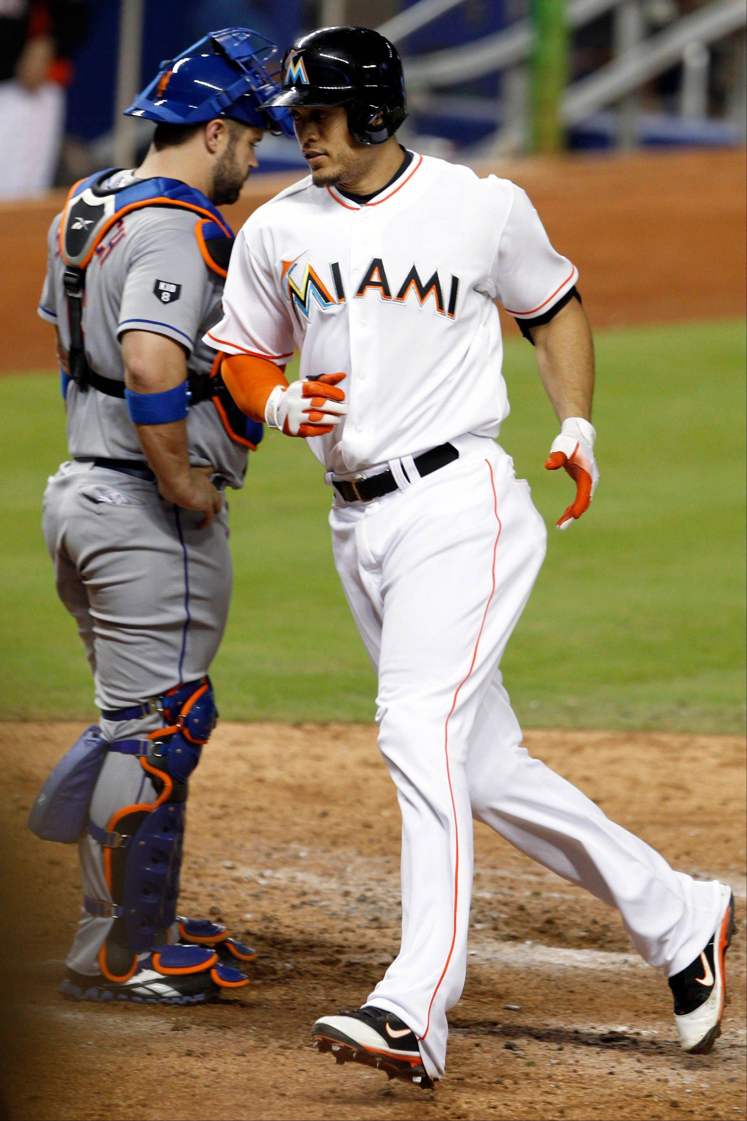 The Marlins' Giancarlo Stanton crosses the plate after hitting a home run in the sixth inning Monday in Miami.