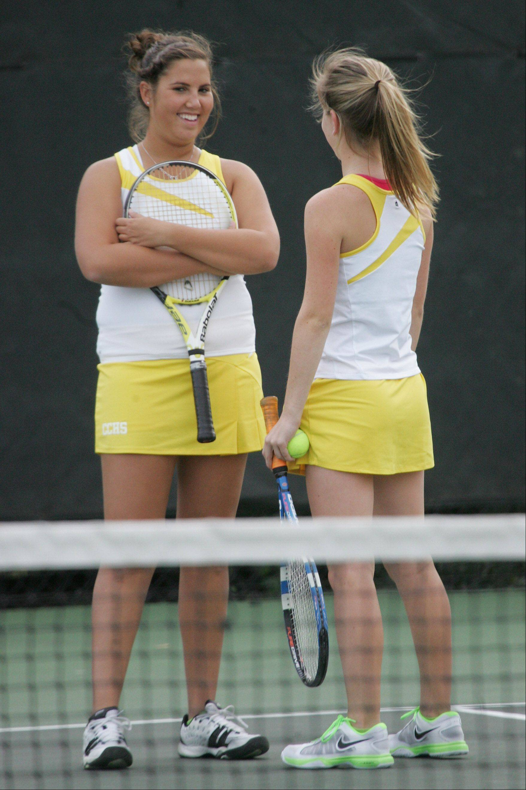 Carmel doubles players Maclain Edwards, left, and Emily Rhine talk during their match against Warren's Courtney Sunday and Mikayla Schultz on Monday in Mundelein.