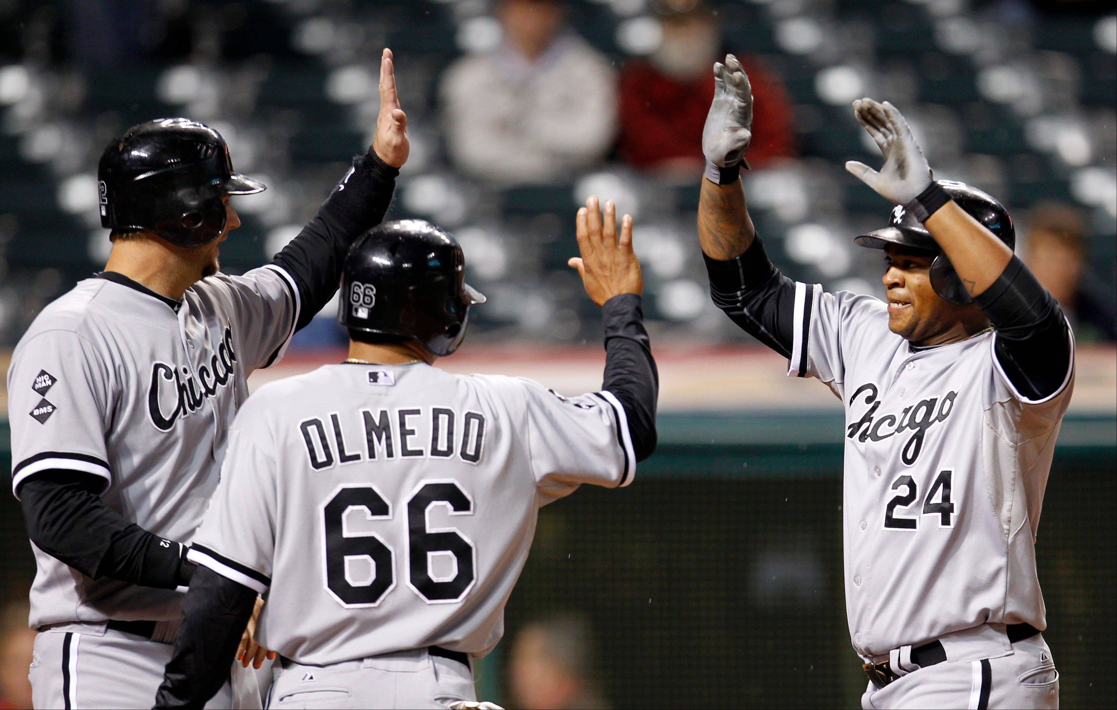 Dayan Viciedo, right, is congratulated by A.J. Pierzynski, left, and Ray Olmedo after Viciedo hit a grand slam in the ninth inning Monday in Cleveland. Pierzynski, Olmedo and Jordan Danks scored. The White Sox won 11-0.