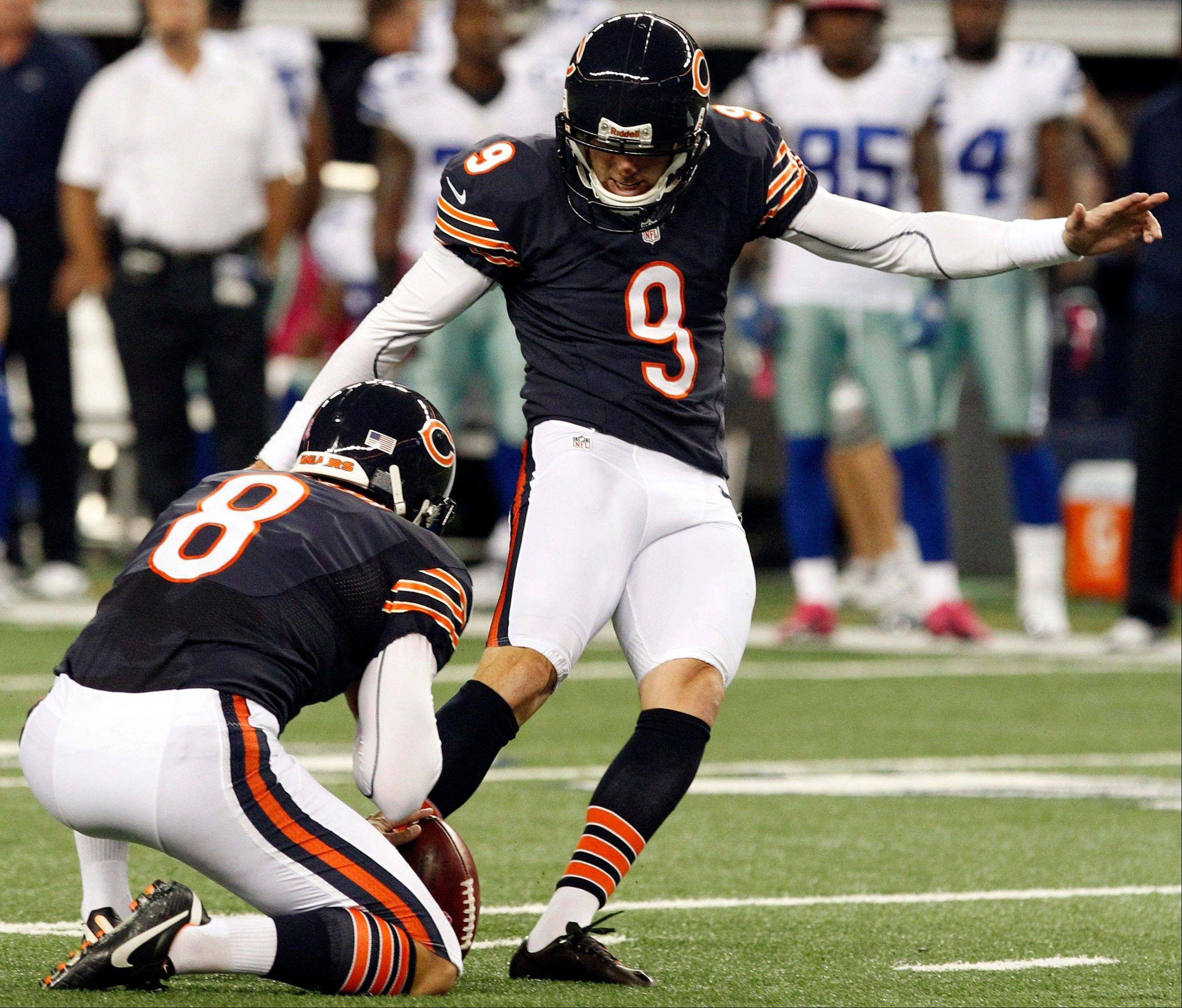Chicago Bears punter Adam Podlesh holds as kicker Robbie Gould makes a field goal against the Chicago Bears during the first half.