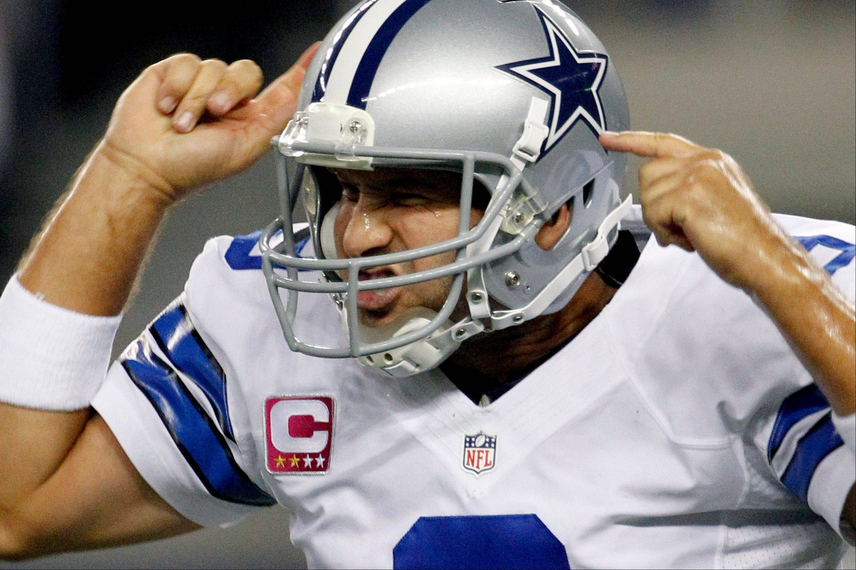 Dallas Cowboys quarterback Tony Romo celebrates his touchdown pass to wide receiver Miles Austin during the first half.