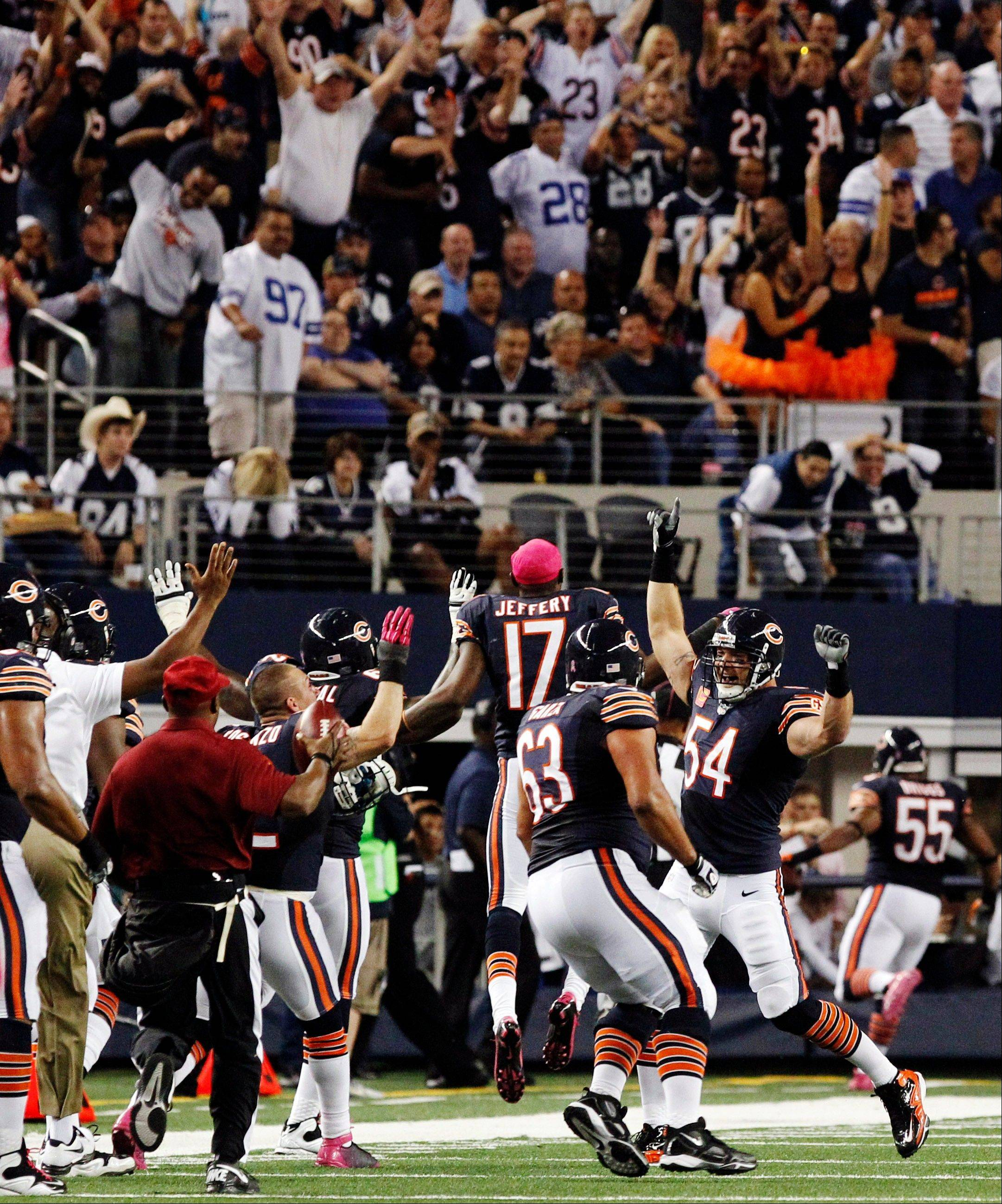 The Chicago Bears bench celebrates as outside linebacker Lance Briggs returns an interception from Dallas Cowboys quarterback Tony Romo for a touchdown during the second half.