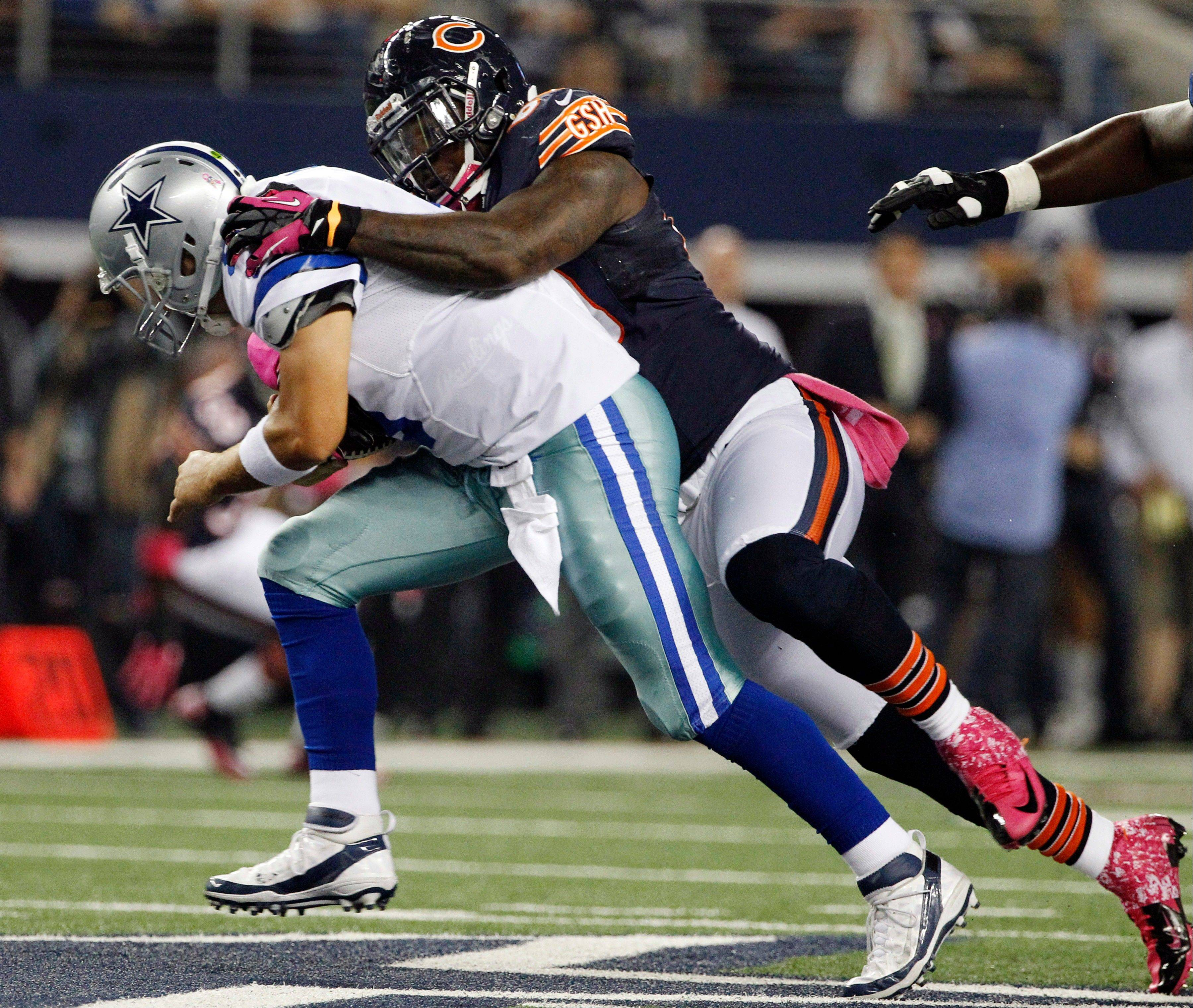 Chicago Bears defensive tackle Henry Melton sacks Dallas Cowboys quarterback Tony Romo during the first half.