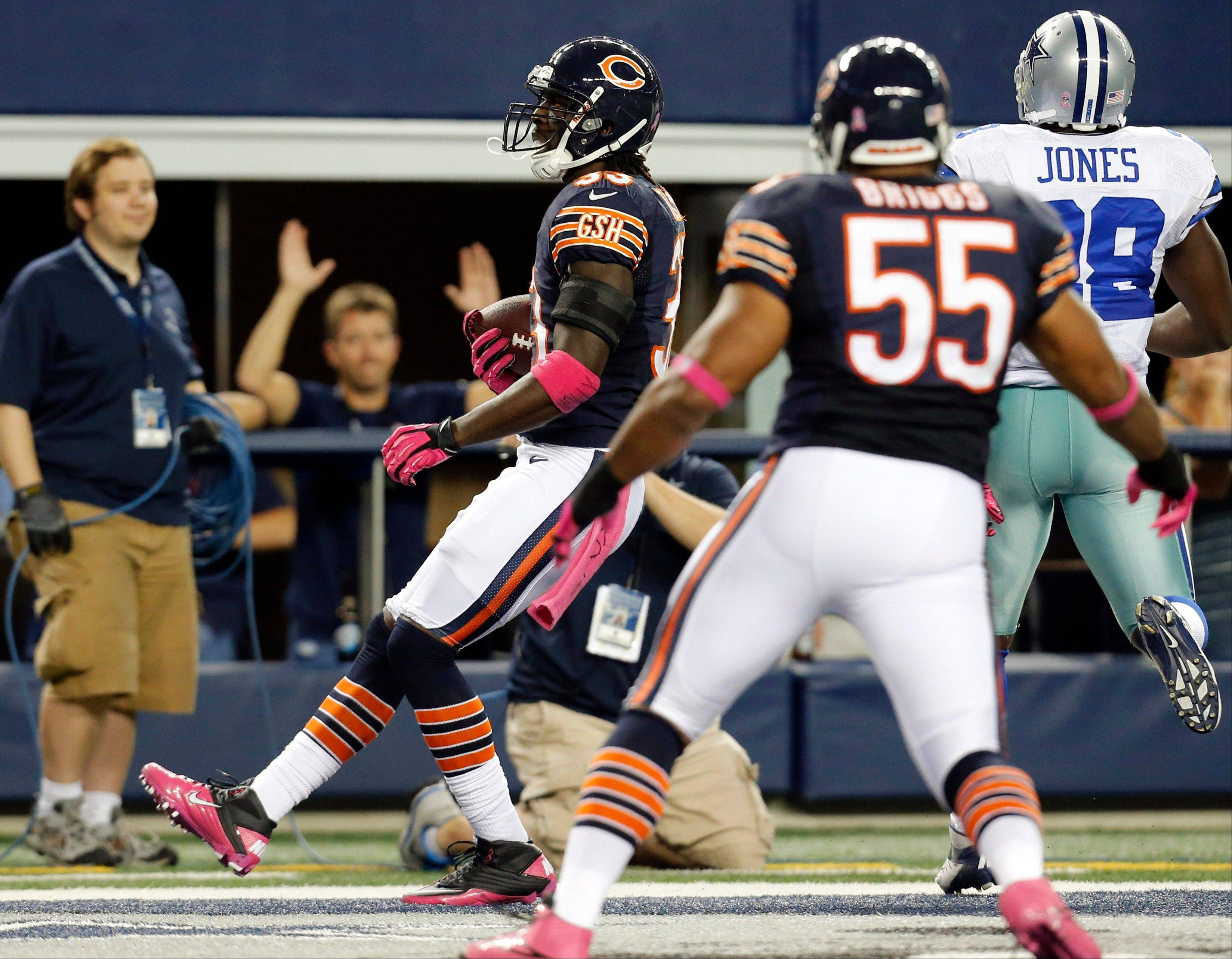 Chicago Bears cornerback Charles Tillman returns an interception for a touchdown past Dallas Cowboys running back Felix Jones as Bears' Lance Briggs watches during the first half.