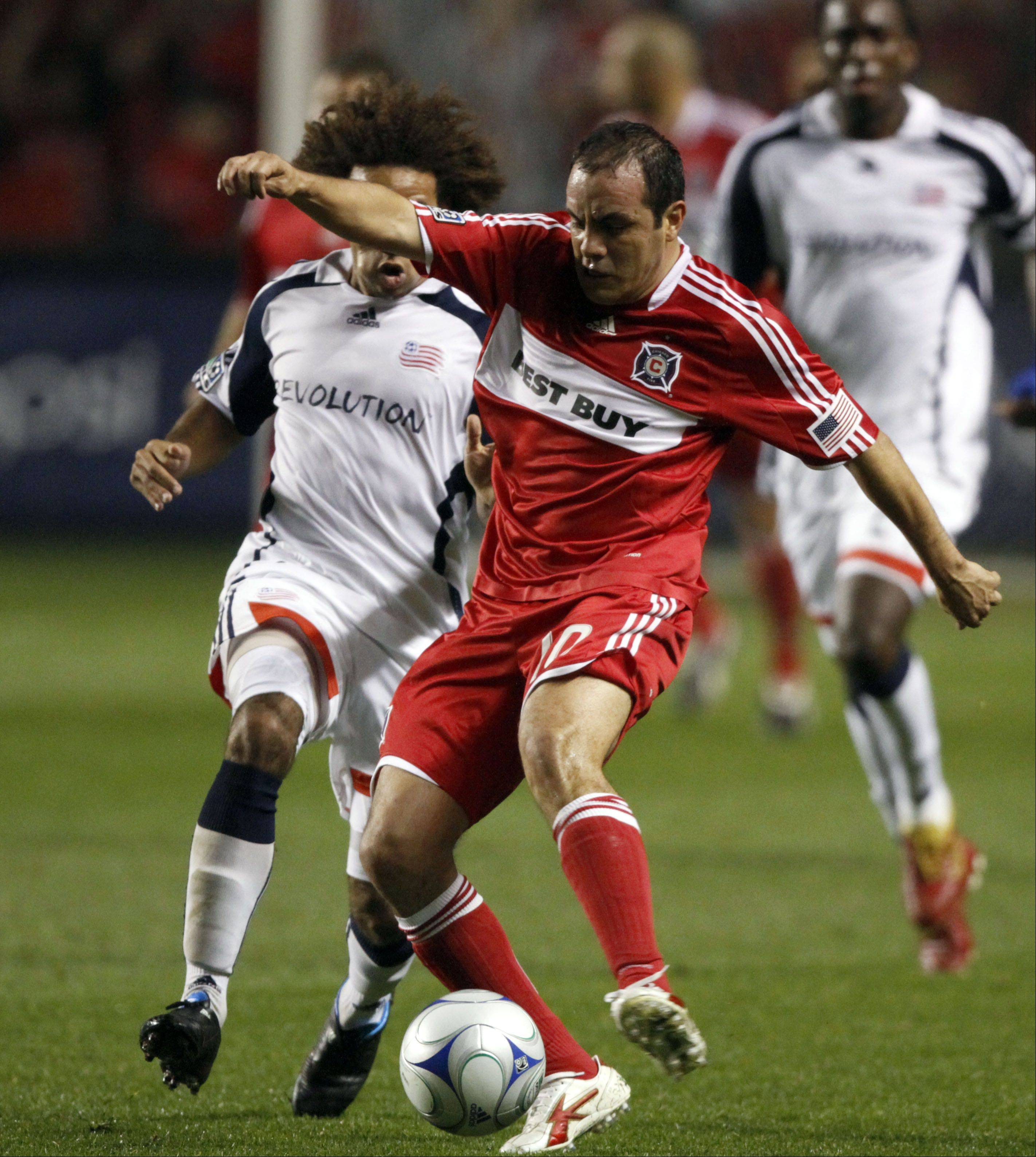New England Revolution's Kevin Alston, left, defends as Chicago Fire's Cuauhtemoc Blanco moves the ball upfield during the first half of an MLS soccer match Saturday, Nov. 7, 2009, in Bridgeview, Ill.