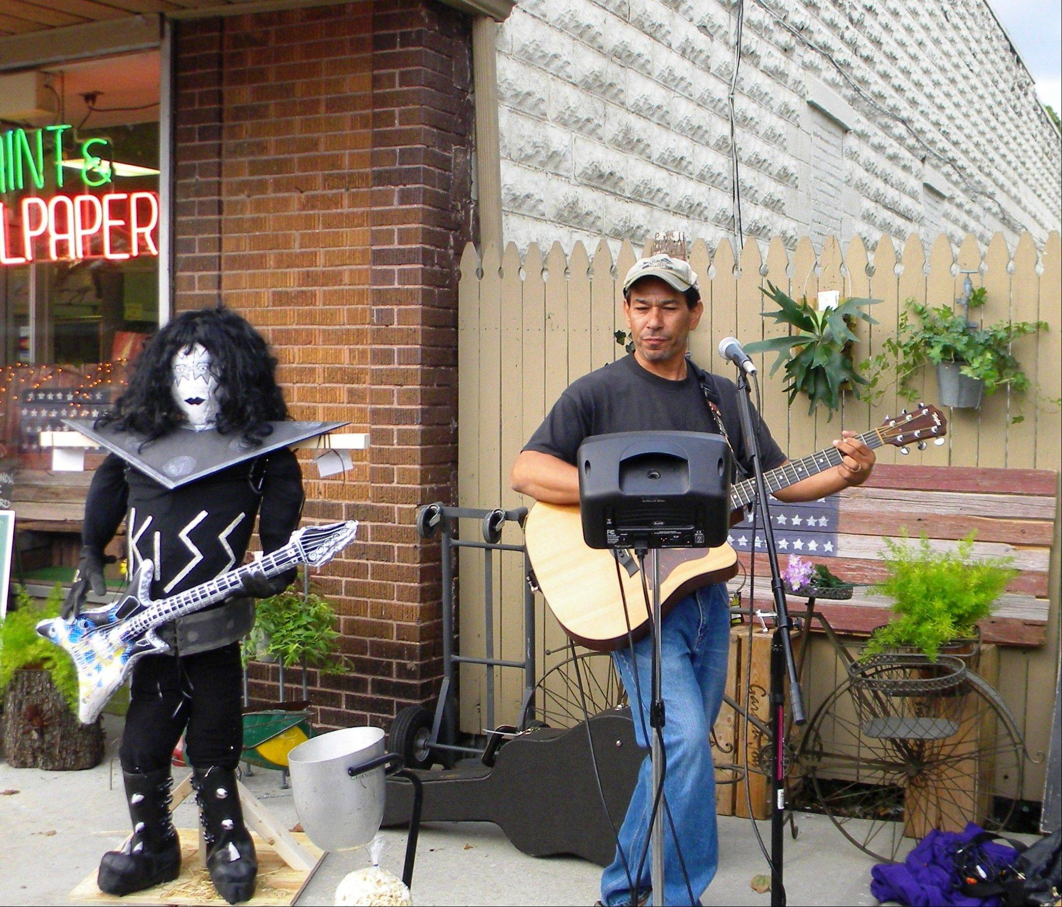 Local musician, Jeff Trudell, adopts a new member for his gig at the Wauconda Area Chamber of Commerce's Scarecrows on Main event.