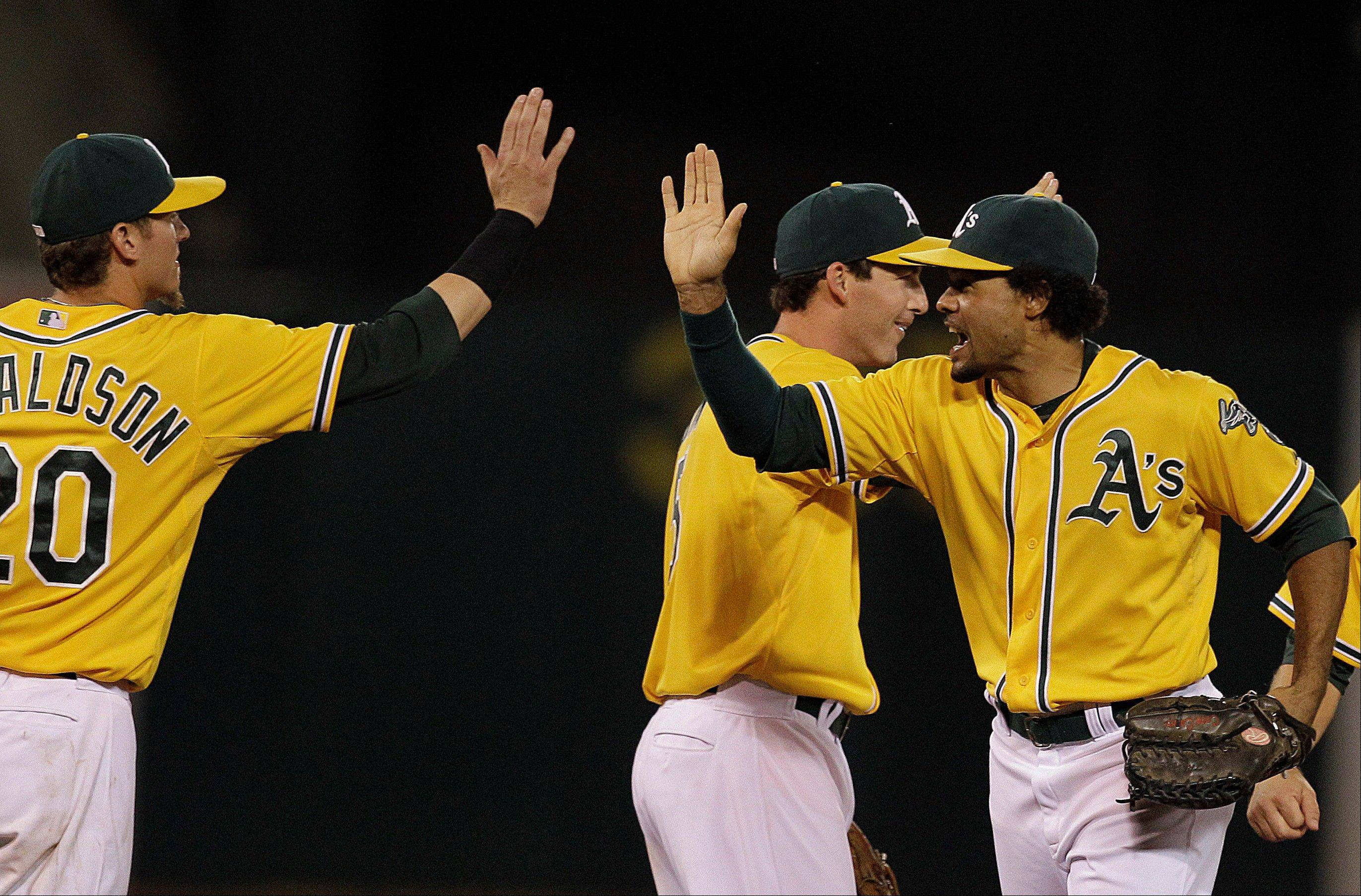 Coco Crisp, right, Josh Donaldson and other Oakland players celebrate Tuesday�s home win against the Texas Rangers.