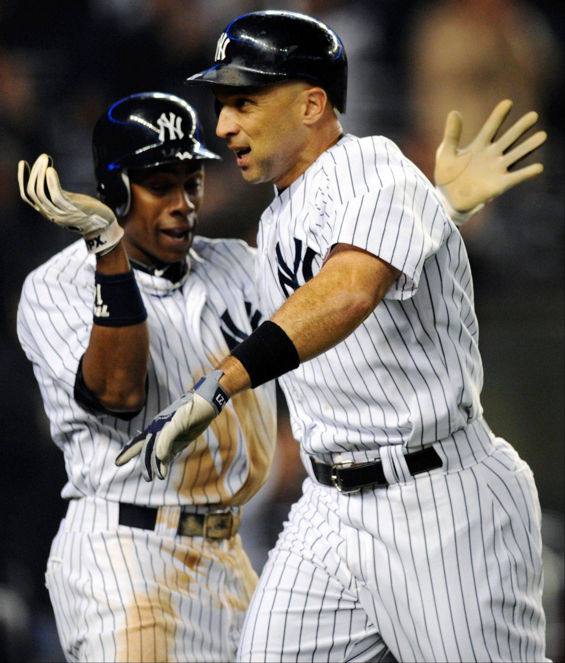 The Yankees� Raul Ibanez, right, is congratulated by Curtis Granderson after hitting a two-run home run against the Boston Red Sox during the ninth inning Tuesday in New York. The Yankees won 4-3 in the 12th inning.