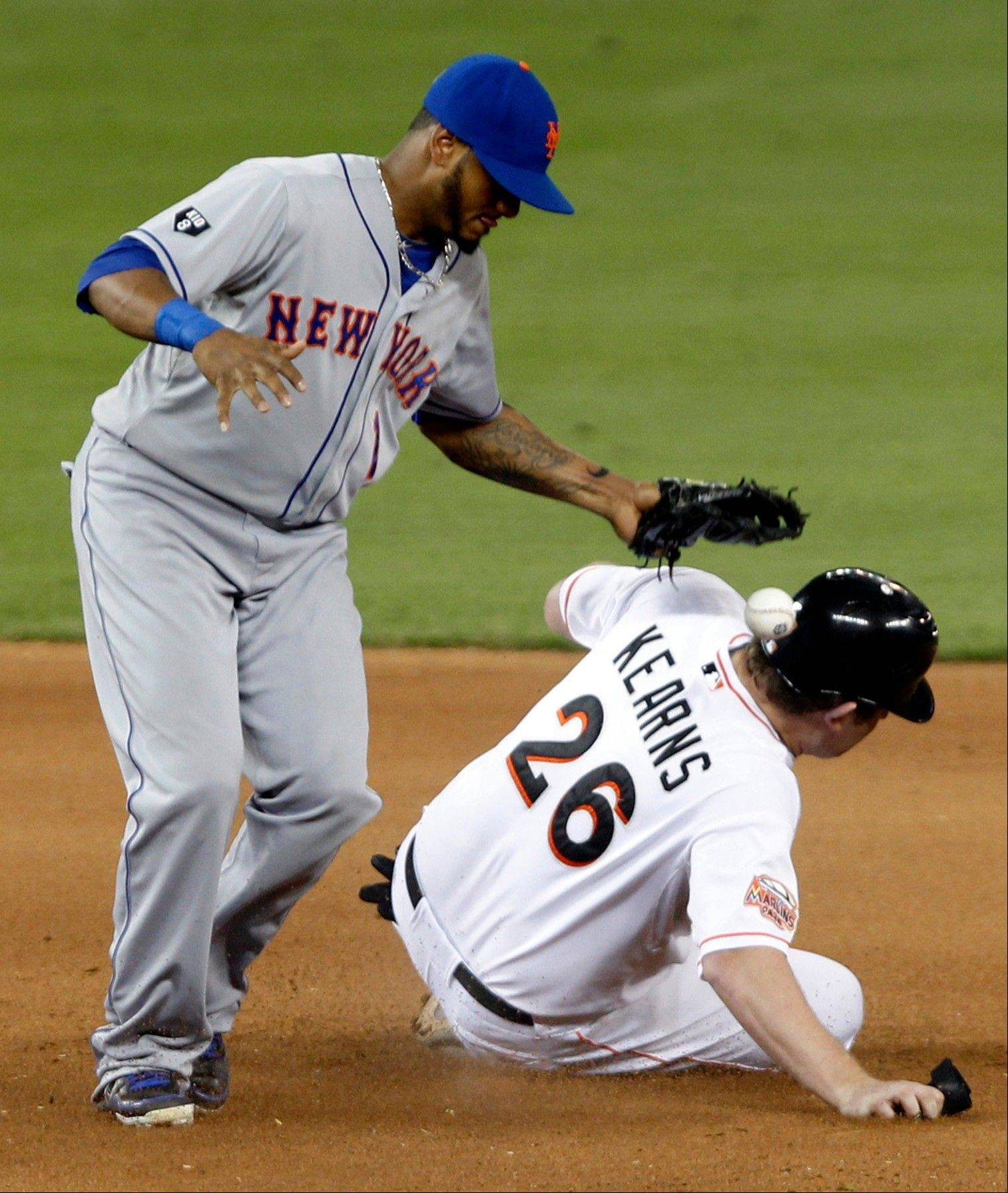 The Marlins� Austin Kearns steals second base as New York Mets second baseman Jordany Valdespin drops the ball in the 10th inning Tuesday in Miami.