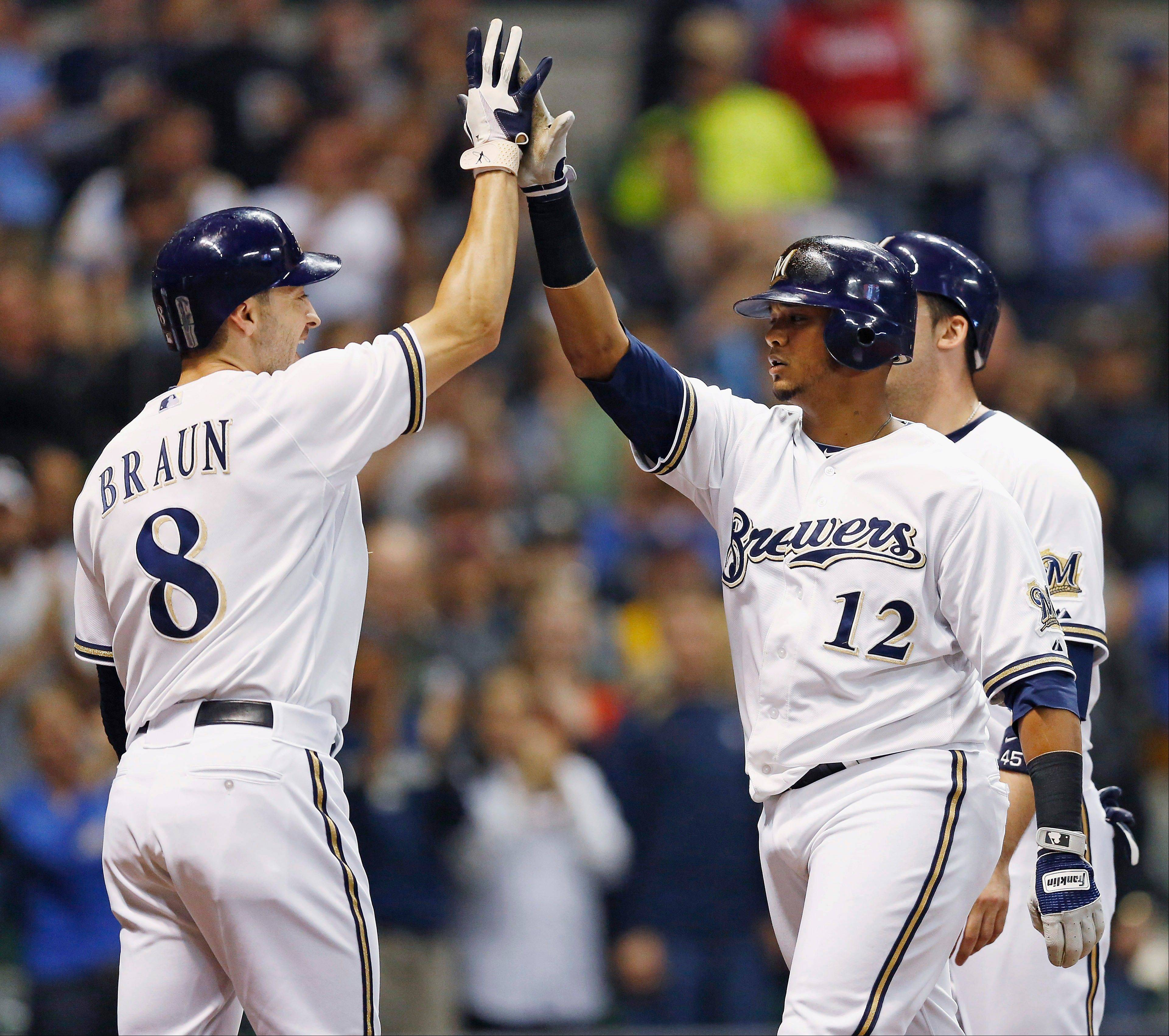 The Brewers� Ryan Braun gives a high-five to Martin Maldonado after Maldonado hit a grand slam off San Diego�s Anthony Bass during the third inning Tuesday in Milwaukee.