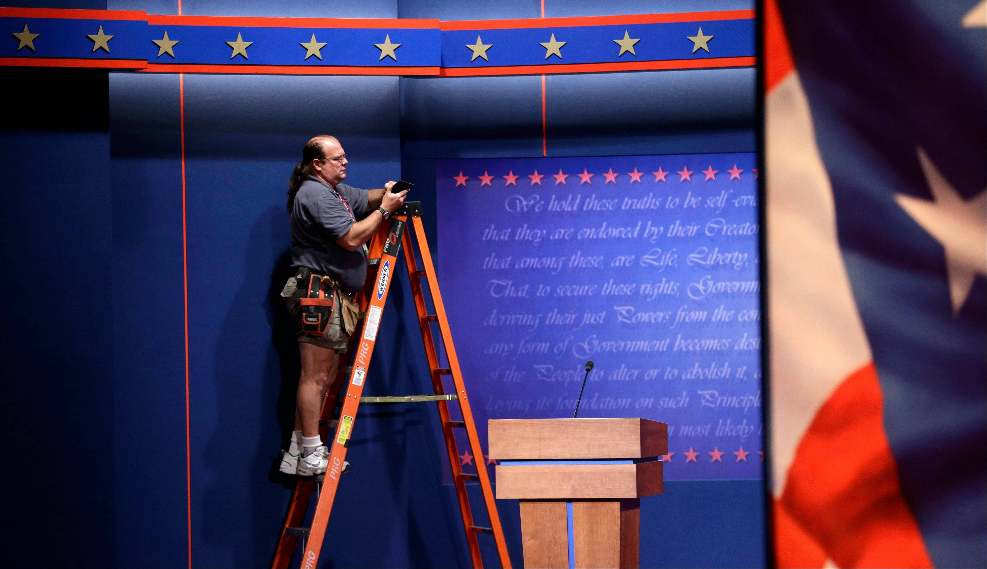 A worker helps prepare the set Tuesday for the presidential debate at the Magness Arena on the campus of the University of Denver in Denver.