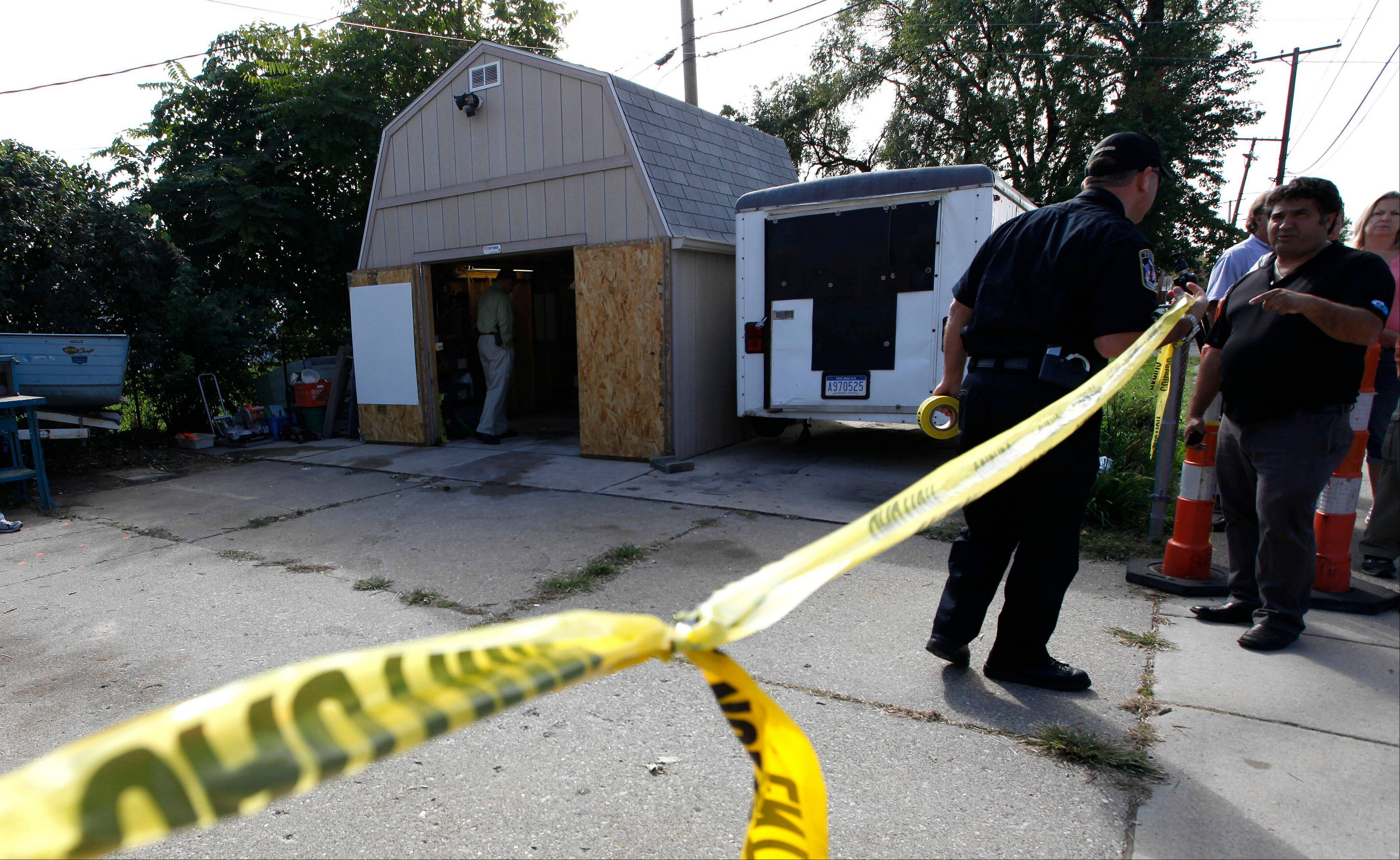 Police tape blocks a driveway where authorities drilled for soil samples in the floor of a shed at a Roseville, Mich.