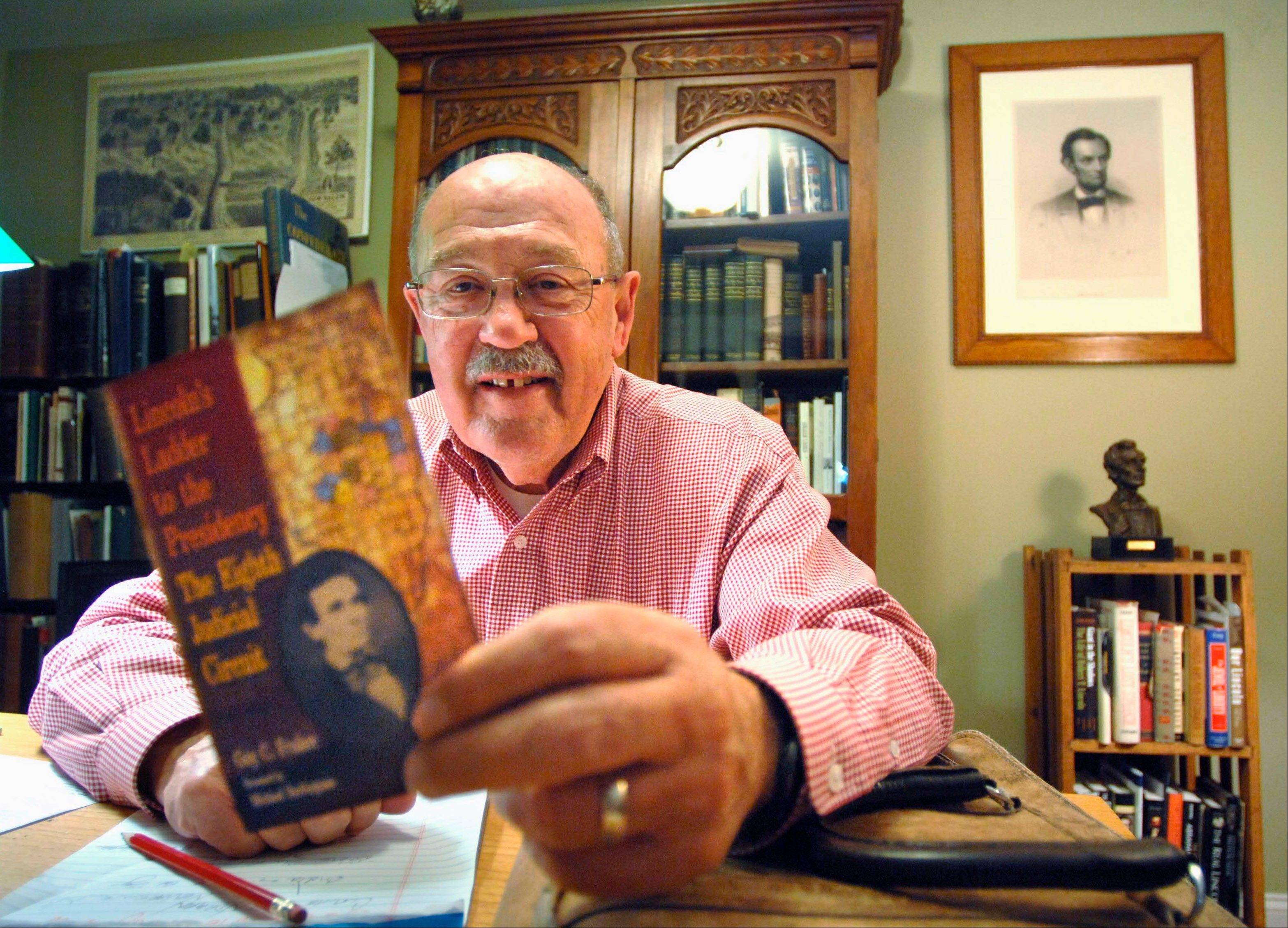 "Guy Fraker, an attorney in Bloomington, Ill., with a flyer in his office announcing his new book, ""Lincoln's Ladder to the Presidency."" The book is about Abraham Lincoln's years as a circuit-riding lawyer in Central Illinois."