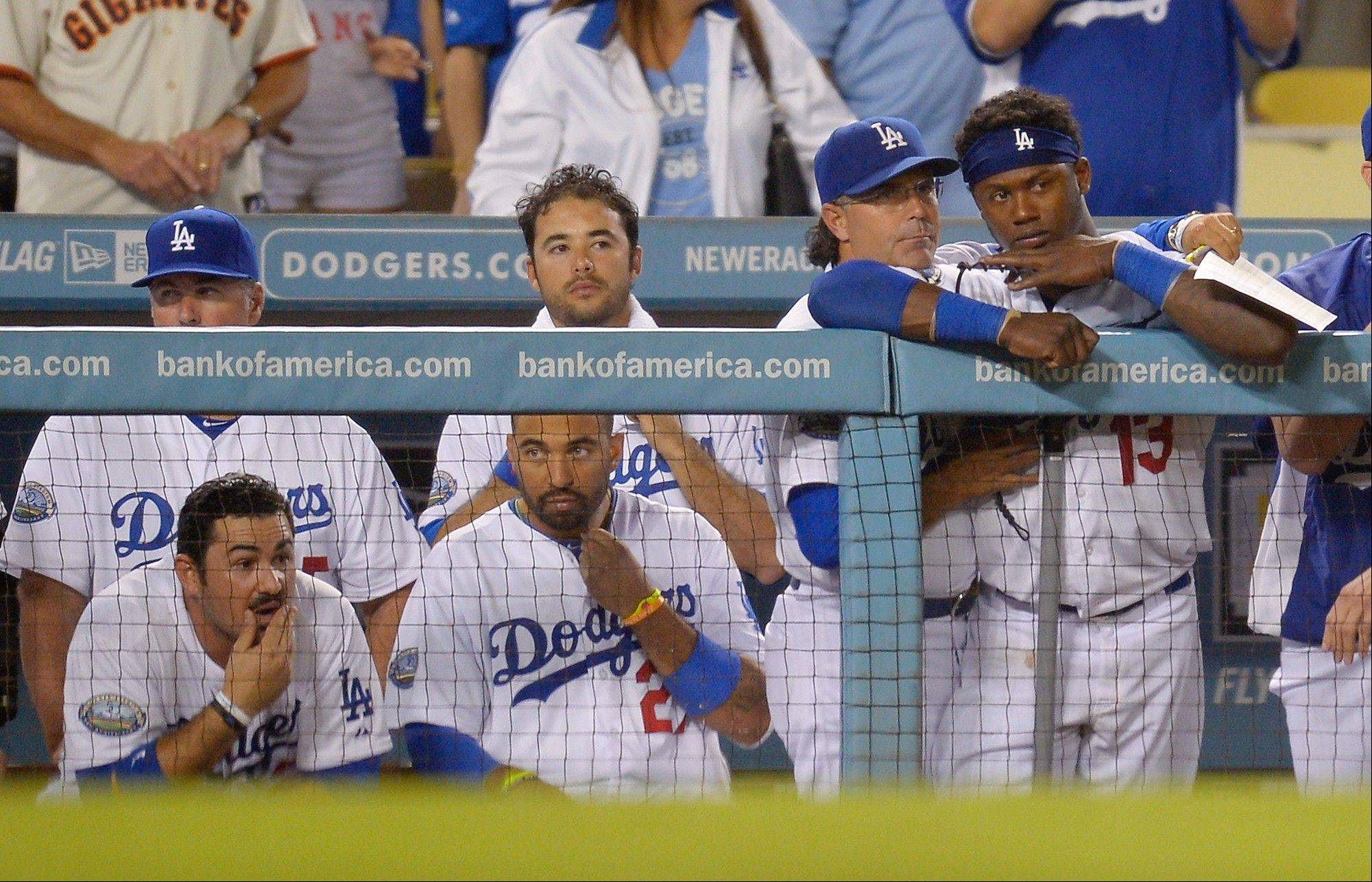 Members of the Dodgers watch from the dugout during the ninth inning Tuesday against the San Francisco Giants. The Giants won the game 4-3 in Los Angeles.