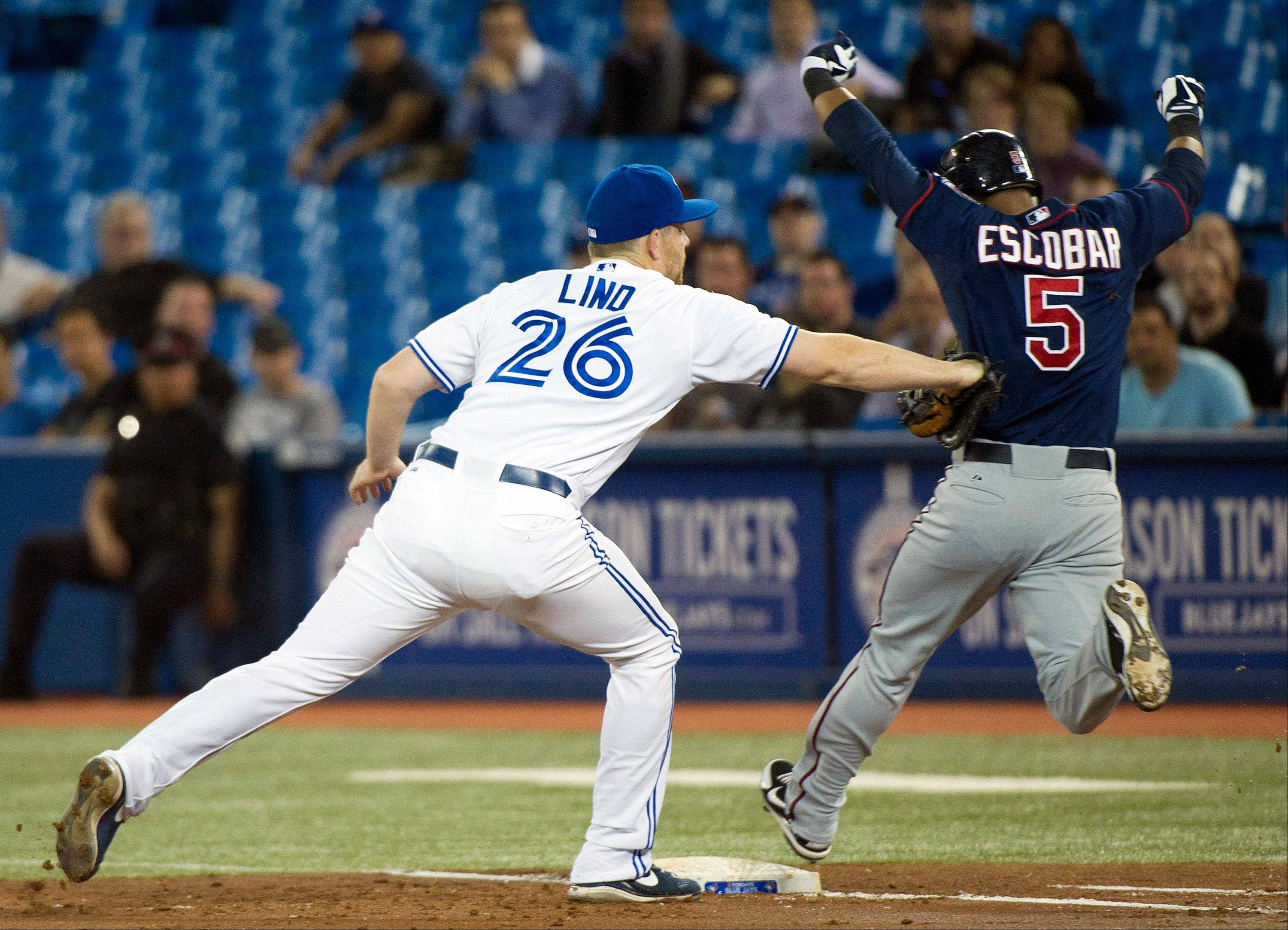 Blue Jays first baseman Adam Lind tags out Minnesota's Eduardo Escobar during third inning Tuesday in Toronto.