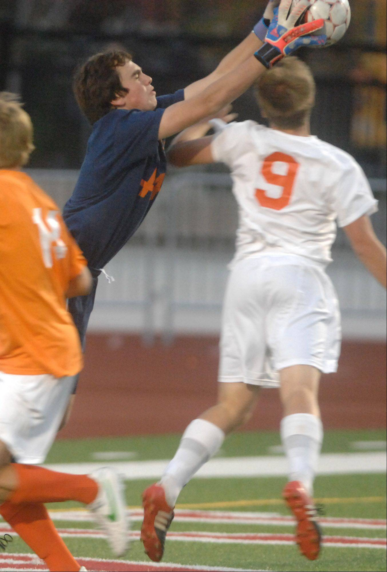 Grant Lesak of Naperville North jumps to catch a shot during the Naperville Central vs. Naperville North boys soccer game in Naperville Tuesday.