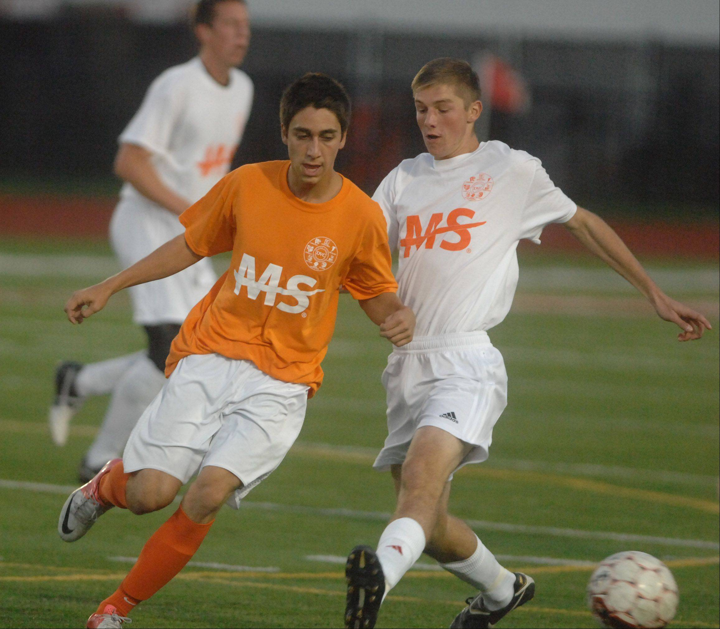Chris MacClean,left, of Naperville North and Jack Burdett of Naperville Central chase down a ball during the Napervile Central vs. Naperville North boys soccer game in Naperville Tuesday.