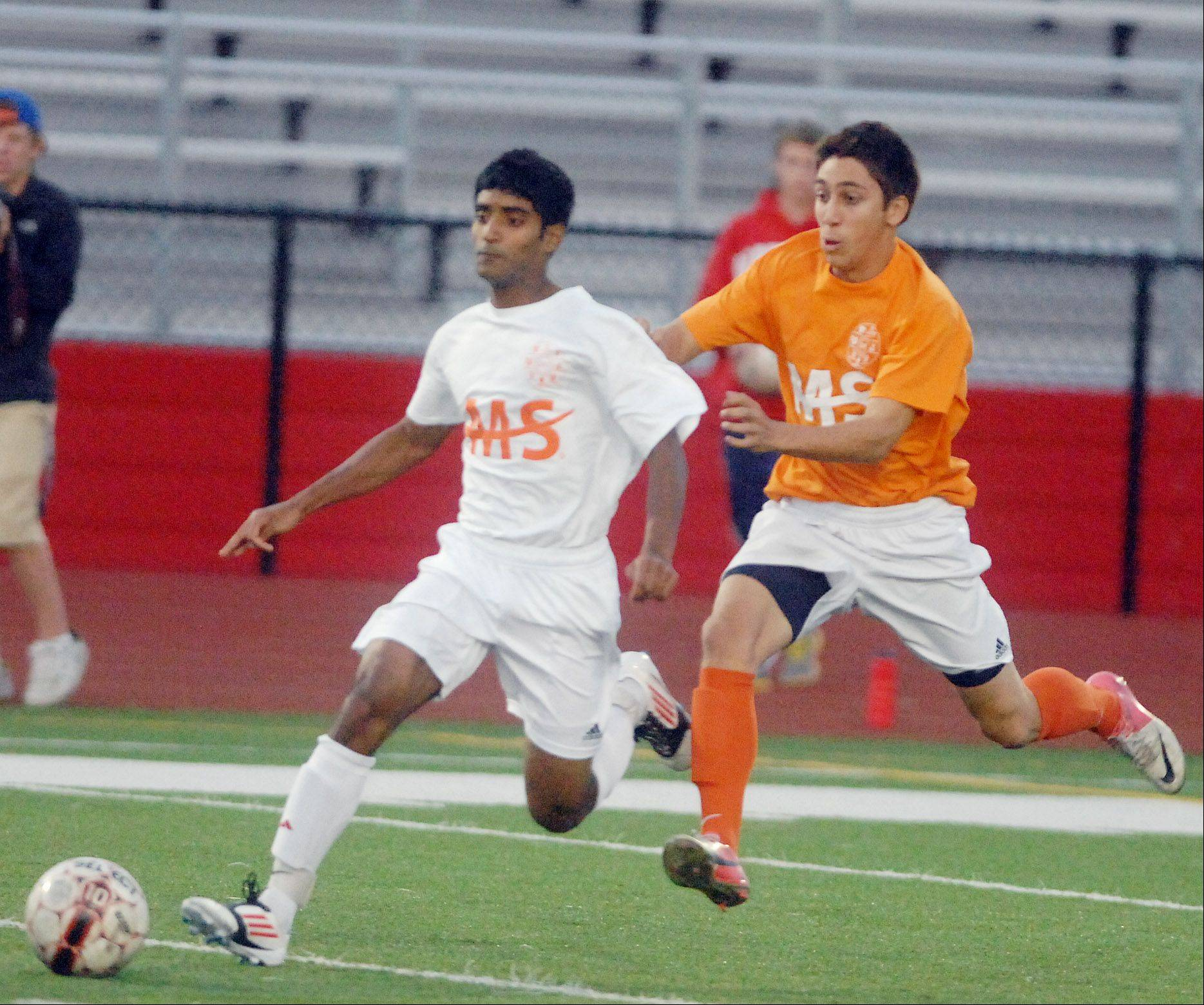 Ajay Varghese,left, of Naperville Central and Chris MacClean of Naperville North chase down a ball during the Napervile Central vs. Naperville North boys soccer game in Naperville Tuesday.