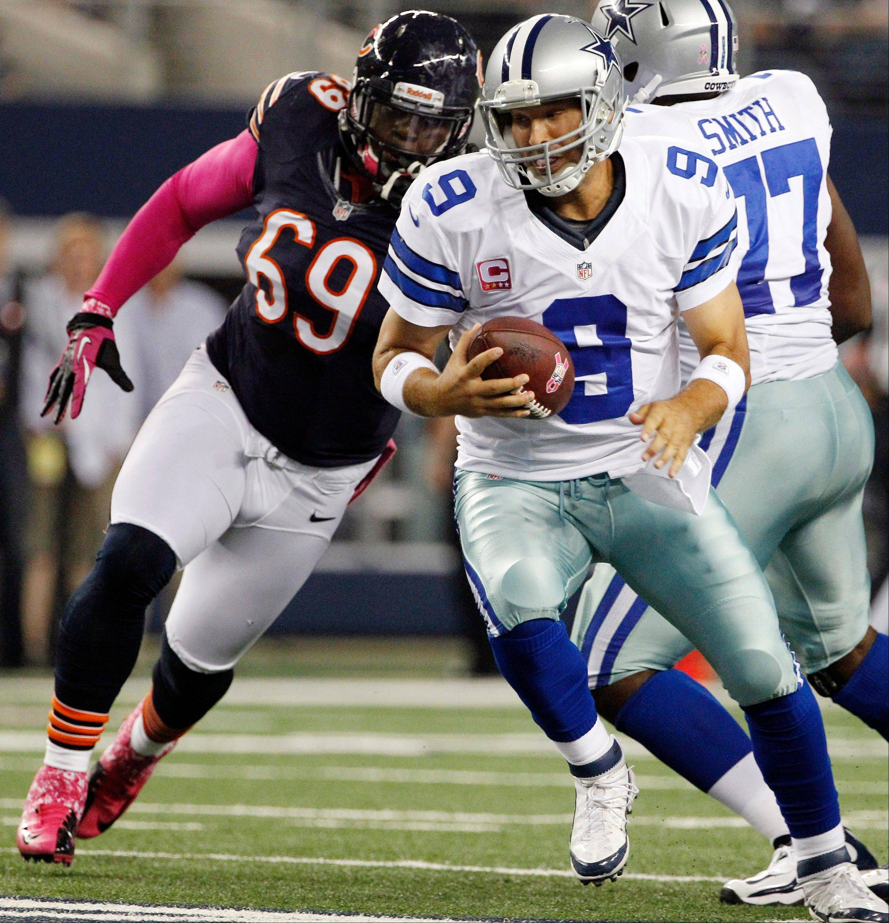 Chicago Bears defensive tackle Henry Melton (69) moves in to sack Dallas Cowboys quarterback Tony Romo (9) during the first half Monday night in Arlington, Texas.