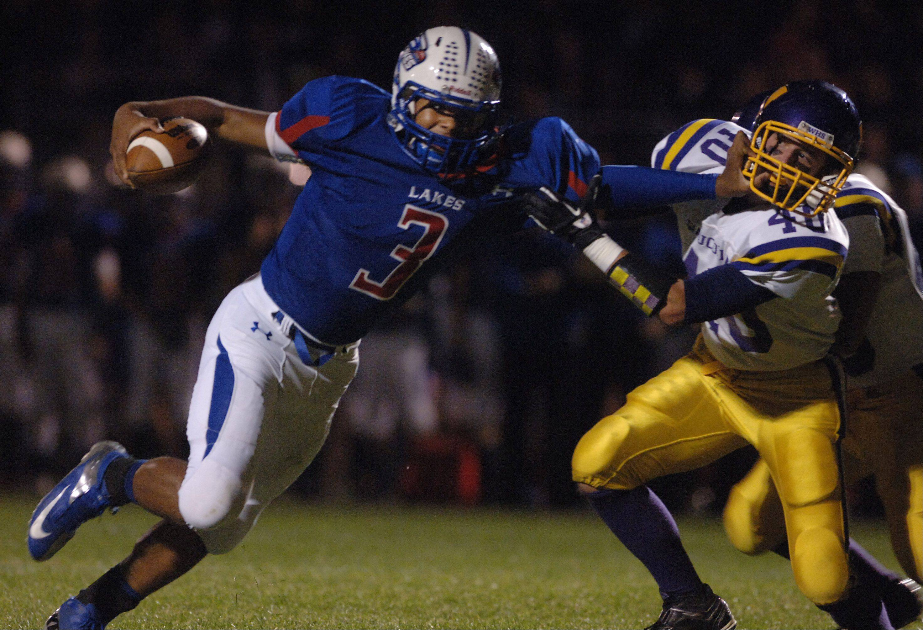 Lakes' T. J. Edwards, 3, stiff-arms Wauconda's Elliot Hill during a running play Friday in Lake Villa.