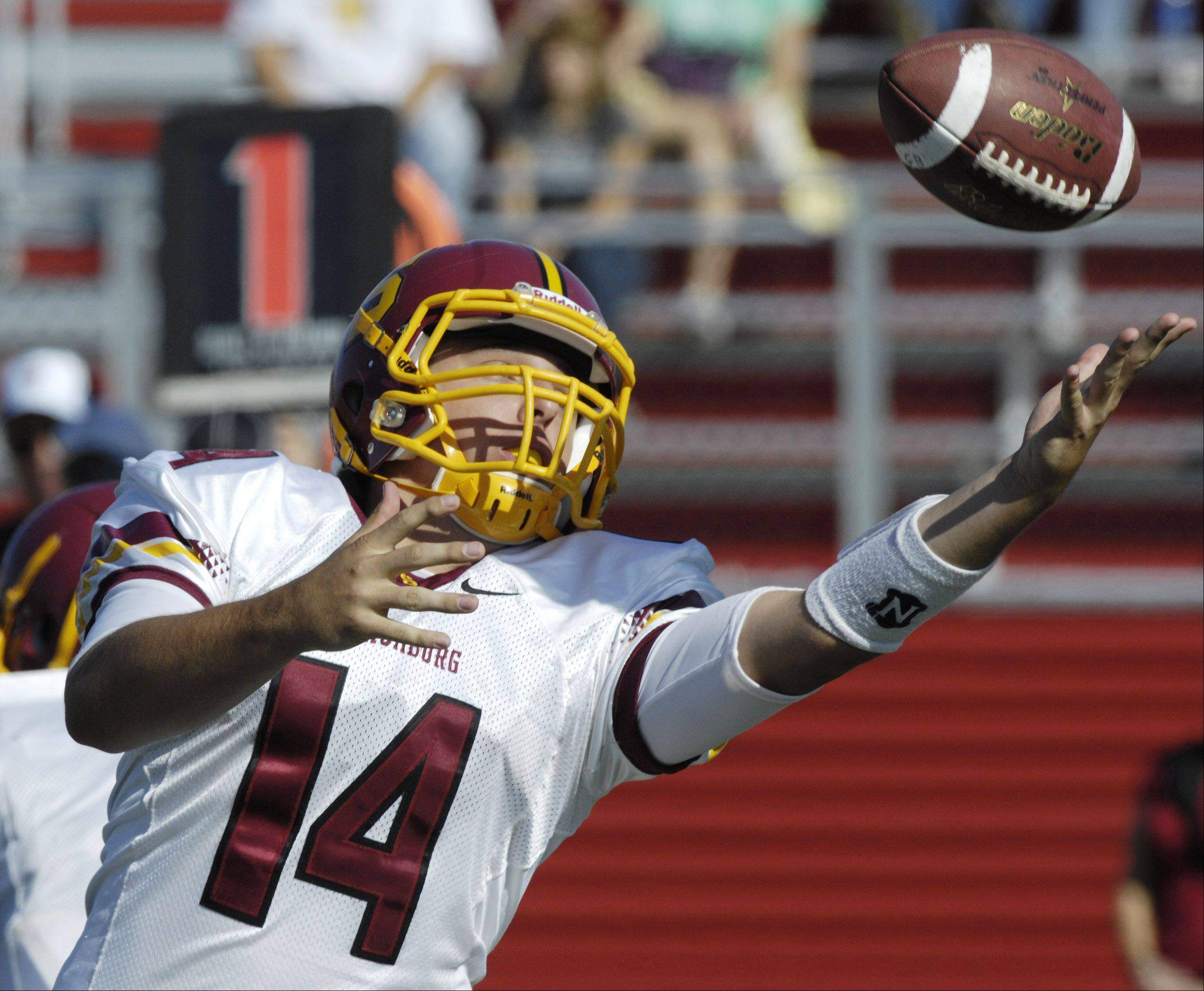 Schaumburg quarterback Nick Anzelmo catches a high snap during Saturday's game against Barrington.