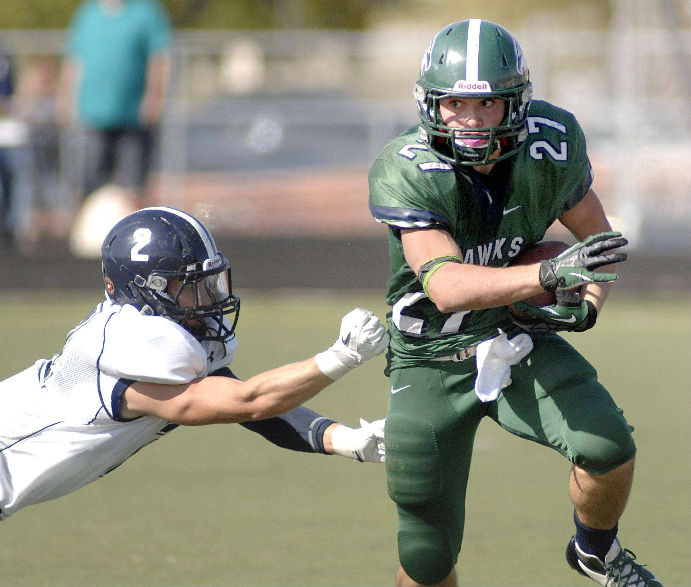 Bartlett's Aaron Everson slips through the fingers of Lake Park's Kevin Teglia during Saturday's football game.
