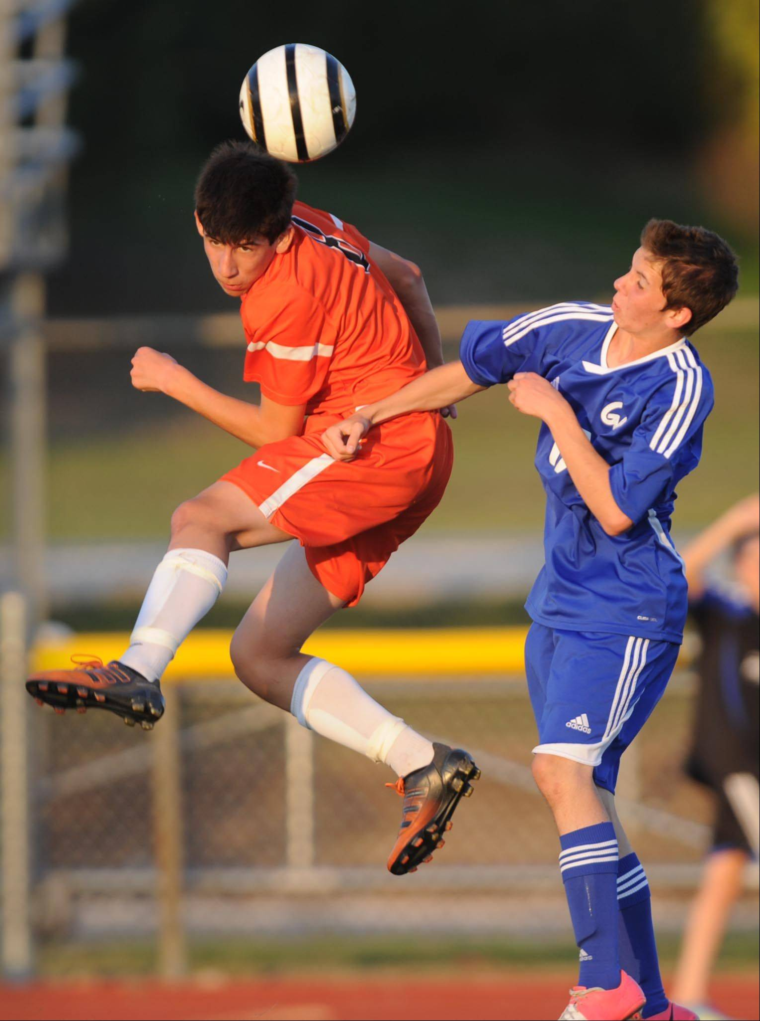 St. Charles East's Taylor Ortiz passes a header as Geneva's Conor Bachte defends Tuesday during the Tri Cities Boys Soccer Challenge at St. Charles East High School.